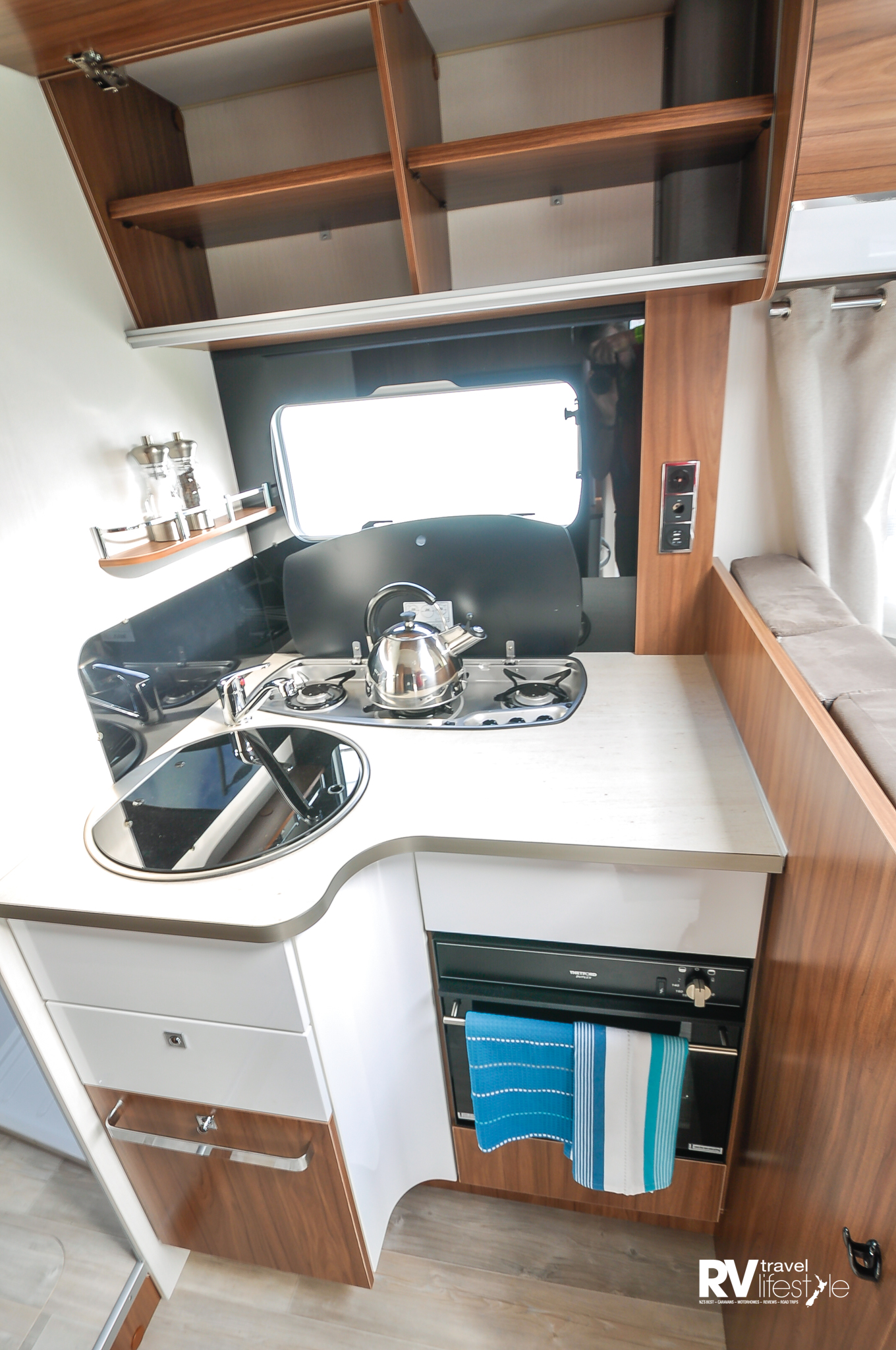 The kitchen has storage cupboards overhead, a utility drawer and a larger storage drawer with a fitted bin. The sink and hob units have glass covers to increase the workspace - not a large space but this is bigger than other European models