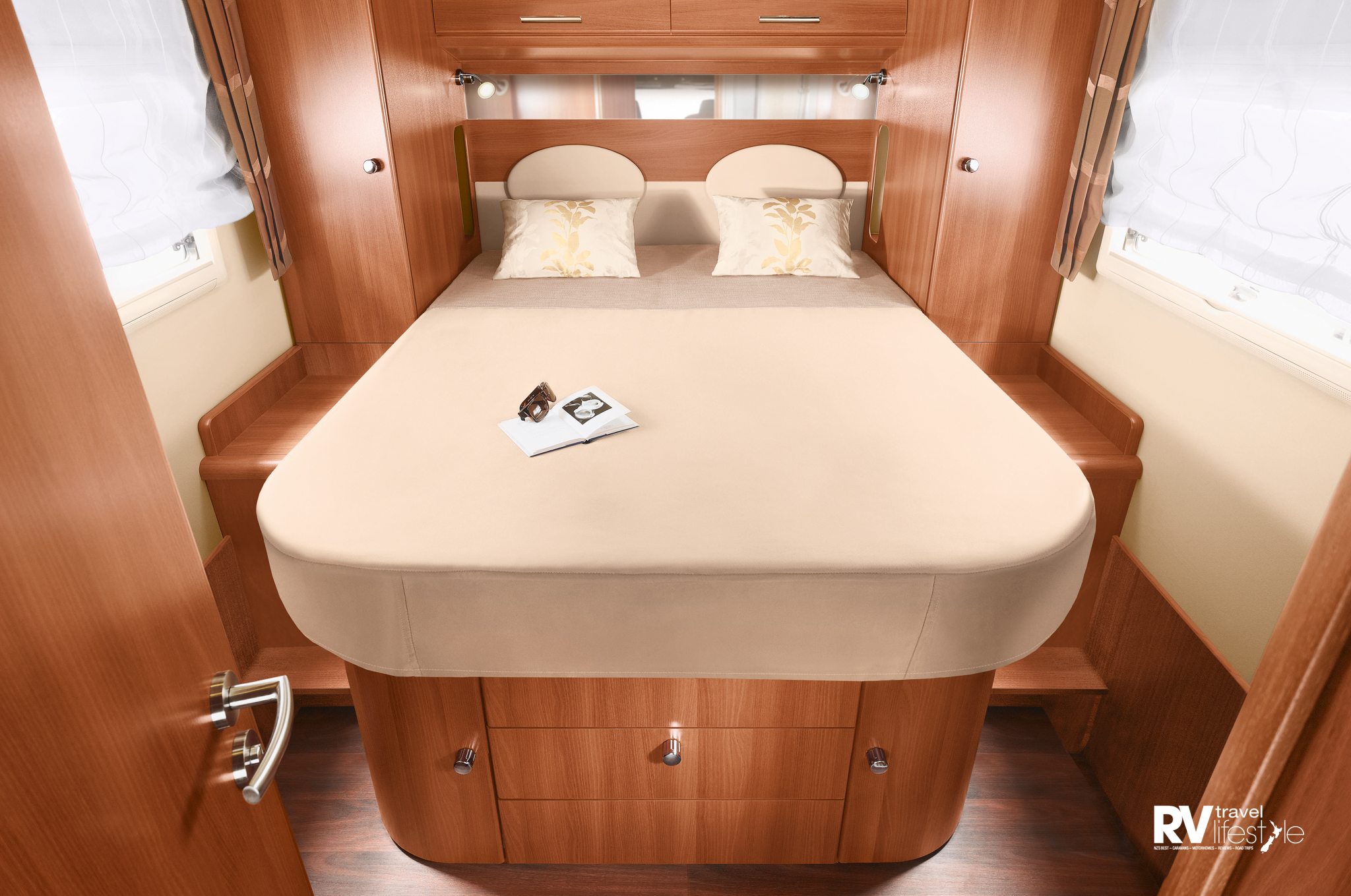The queen-sized island bed has drawer and cupboards below, wardrobes and storage on each side. A privacy door between the en suite and shower area to create a changing area