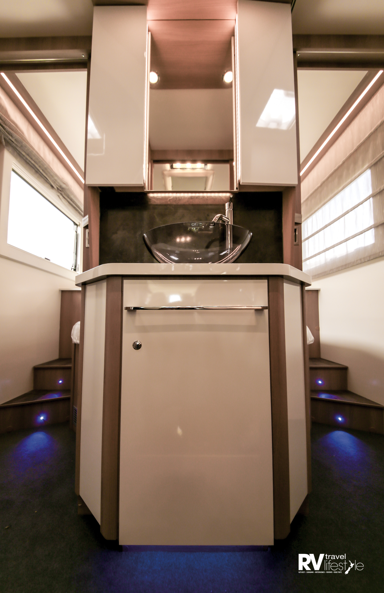 Stylish walk-around sink unit reflects main cabin to create airy feel, or closes off