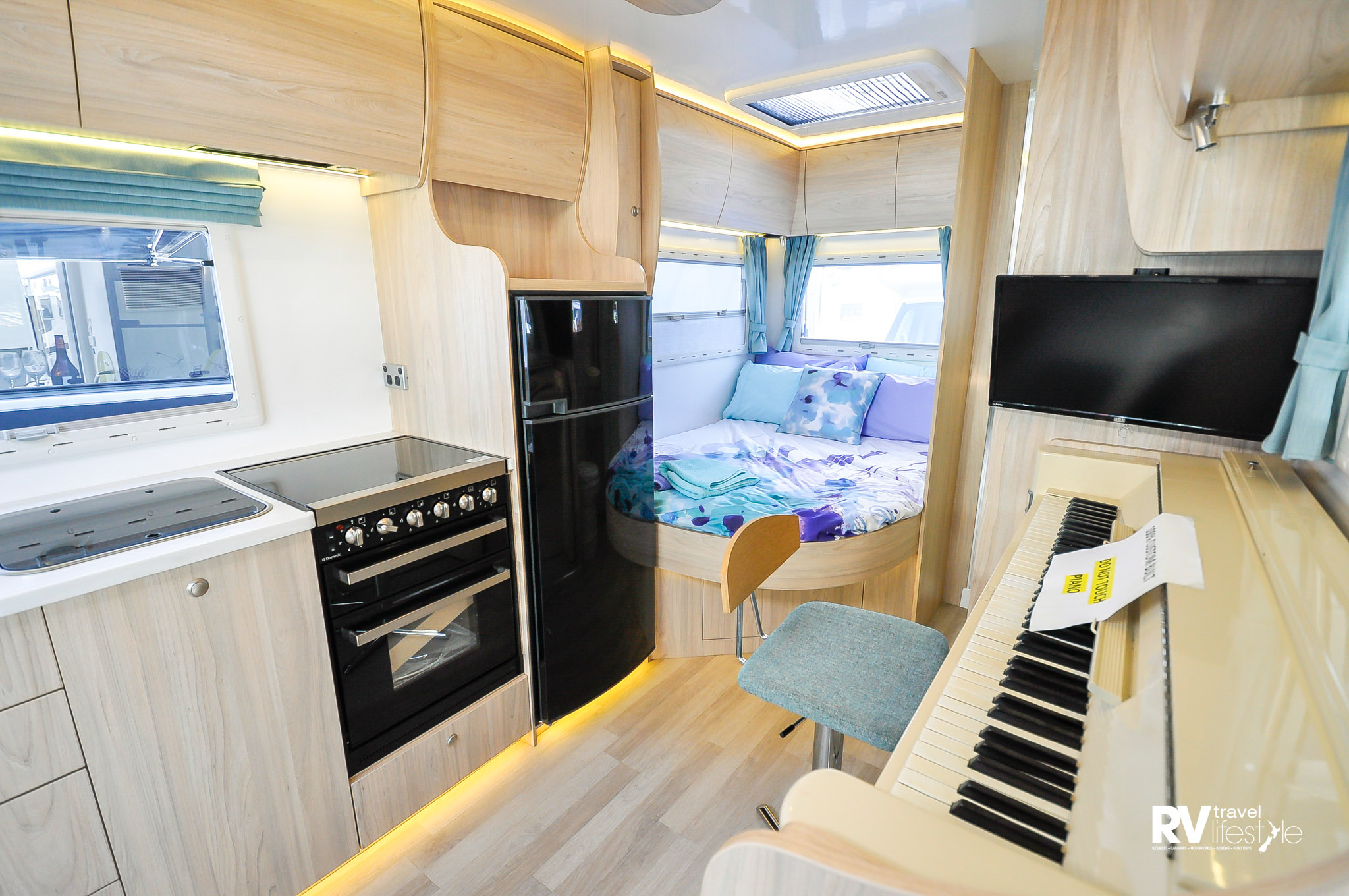 A built-in piano is just one of the features that makes this RV special – note the permanent double-bed