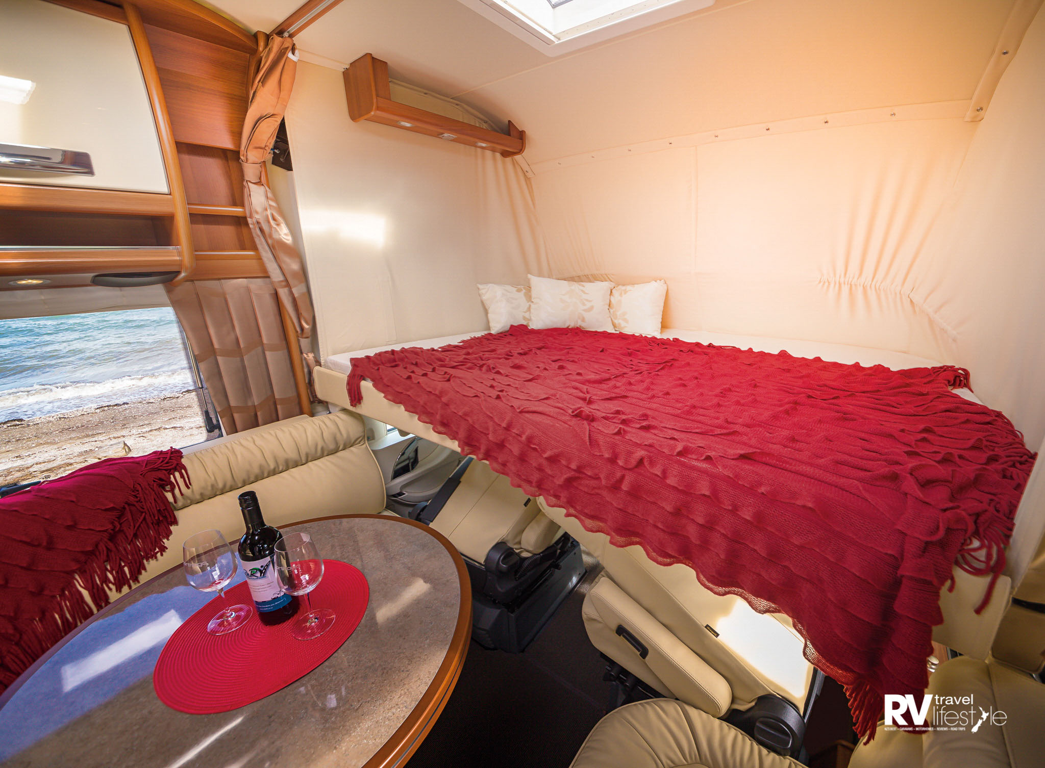 The hidden bed comes down from the ceiling over the front cab area, leaving the dining area free – note the storage shelf and LED lighting up the top, and a pull-across privacy screen