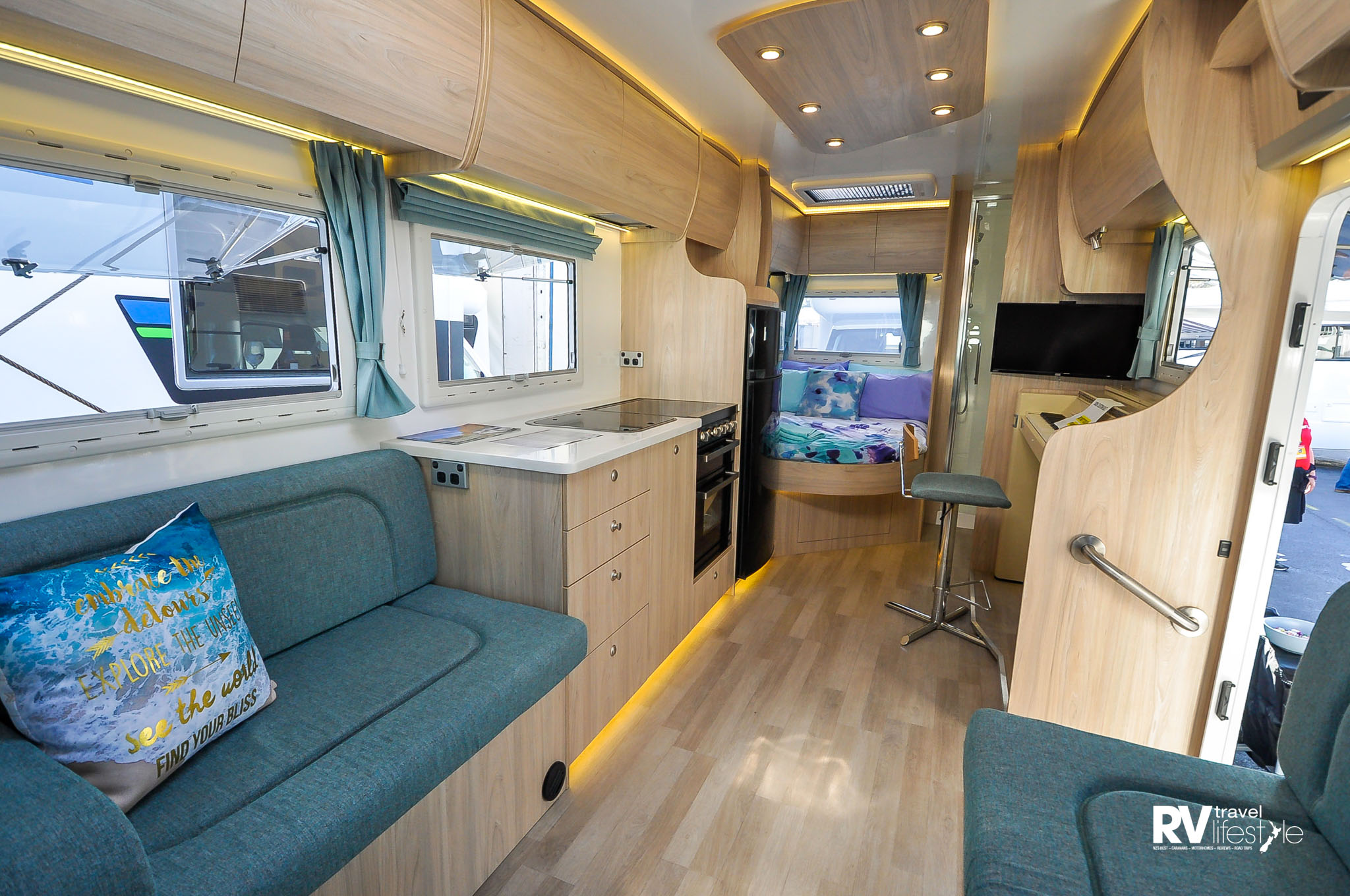 Above & below: The main seating area of the 'piano' RV is just behind the cab, while the cab-over compartment is a storage area