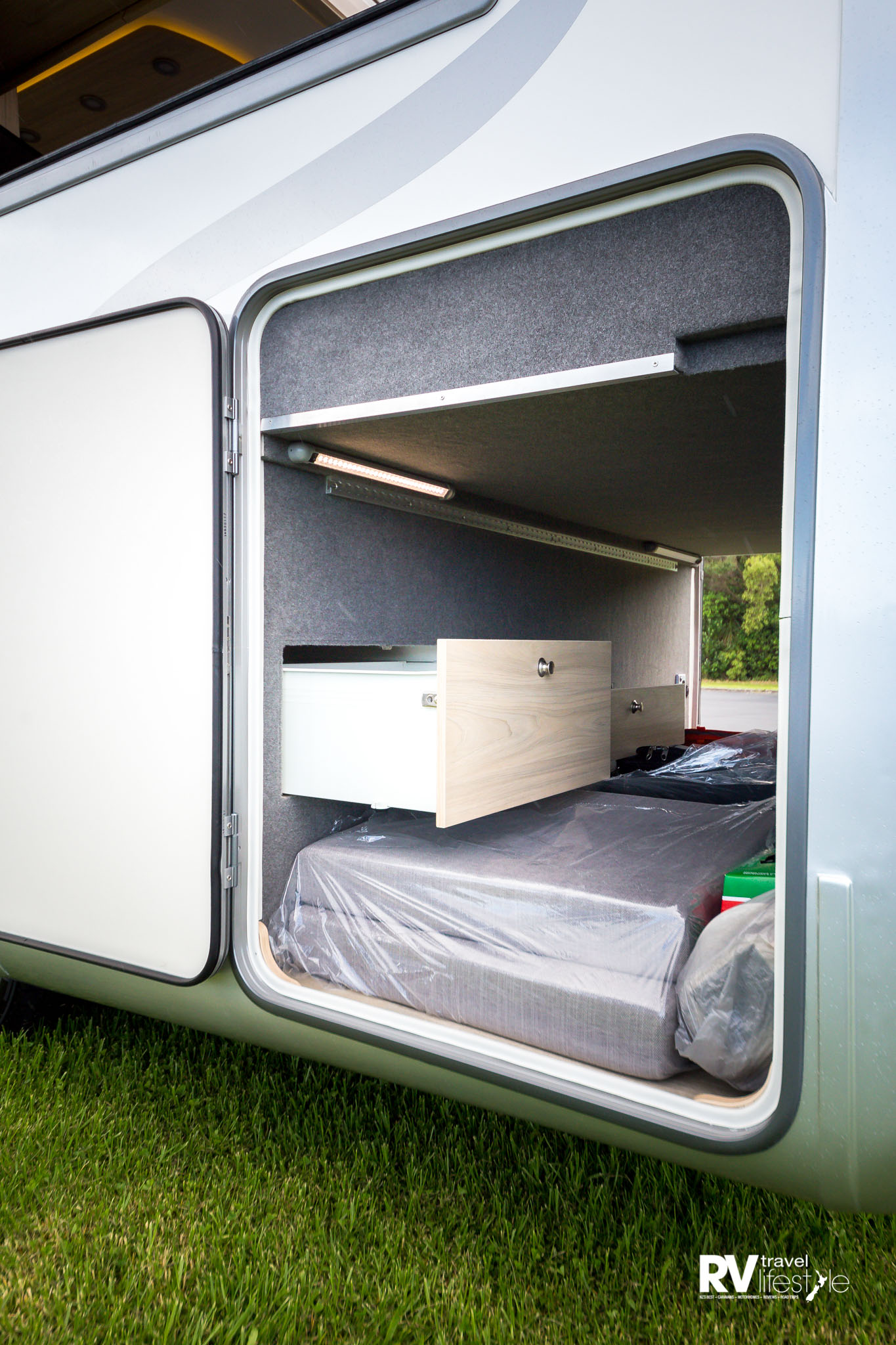 Large rear storage cubby is a feature of both RVs and features pull-out storage drawers