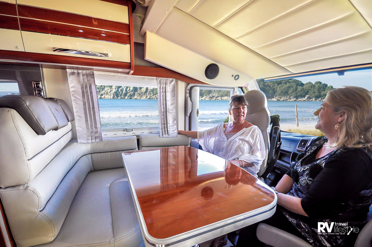 Mobilvetta – the front-cab seats swivel to face the dining area; above them in the ceiling line is a second pull-down bed. This front and cab area is standard across the three models, i.e. the fixed bedroom, single bed and L-shaped rear-lounge ceiling bed