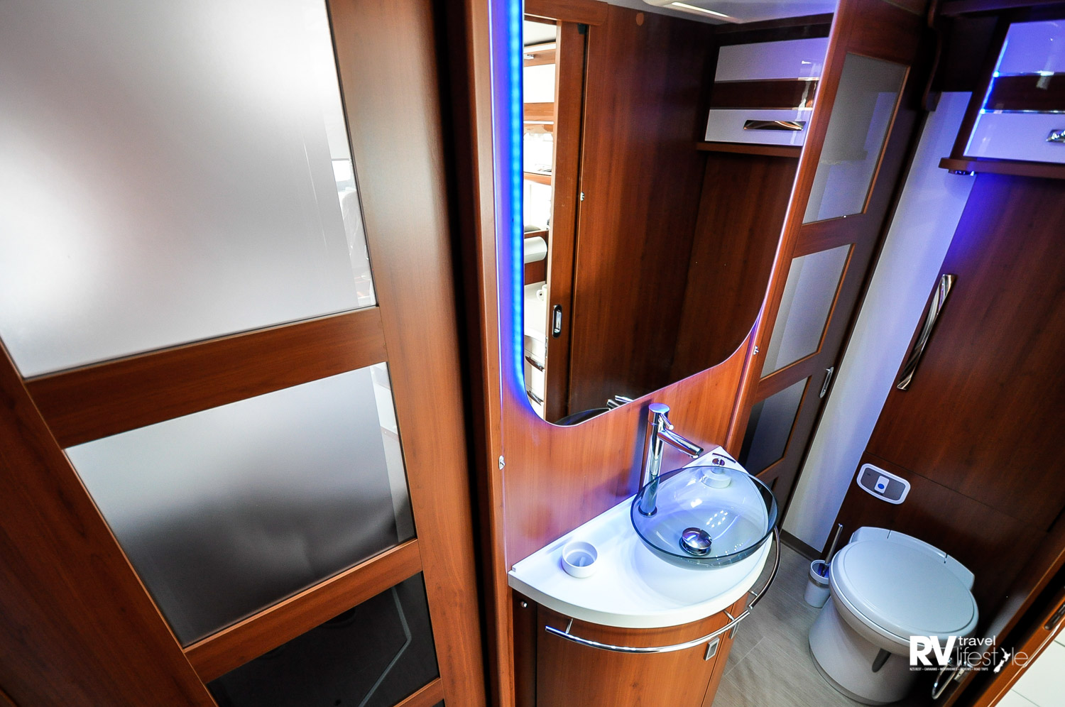 Bathroom in the K-Yacht 79 separate-bedroom model. The sliding glass doors give privacy between the ensuite, front living area and the bedroom. LED lighting throughout, full separate shower on one side, toilet and vanity the other