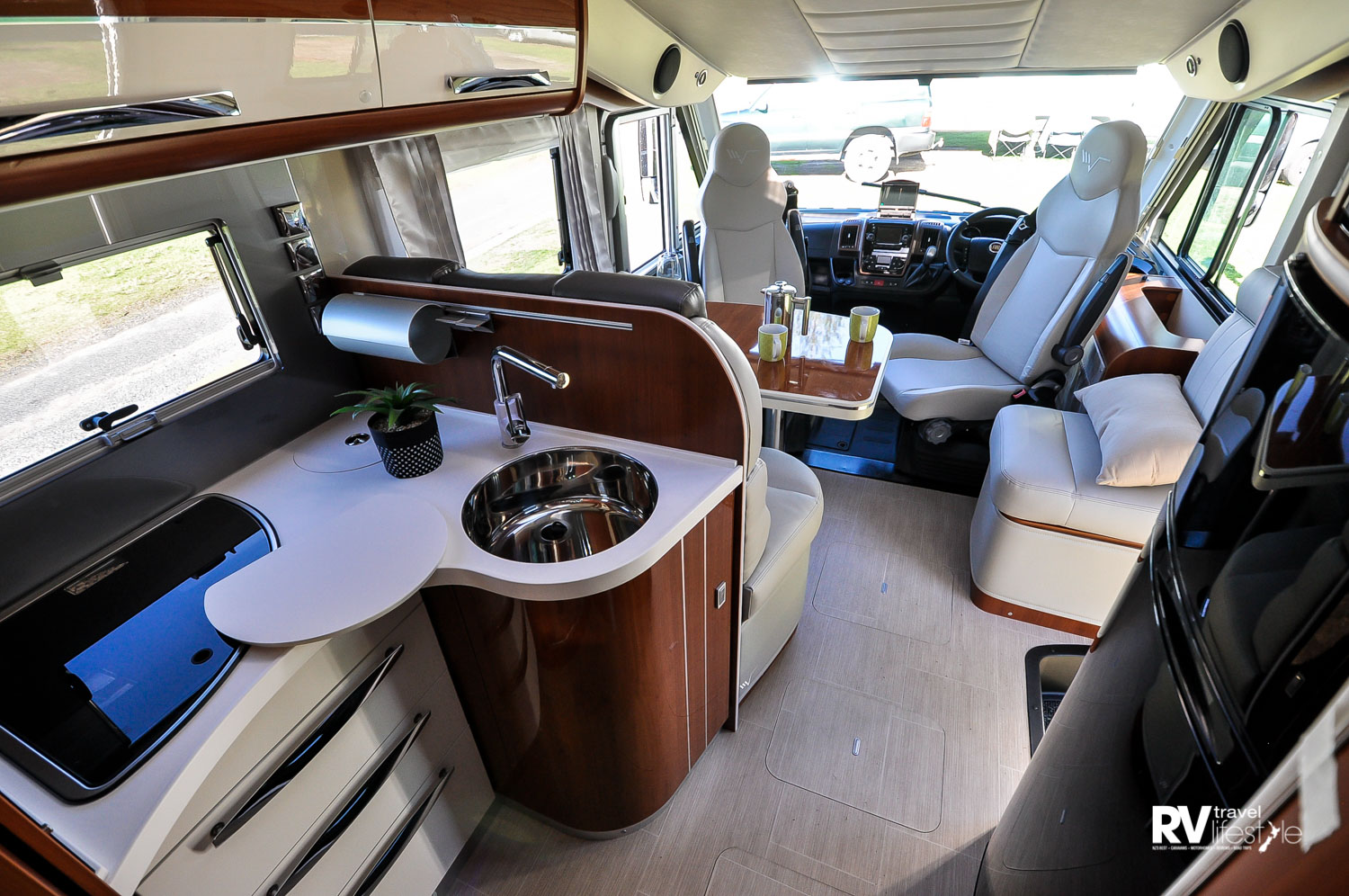 The kitchen in the K-Yacht 80: drawers below the gas hob, the sink lid doubles as a chopping board, the rubbish bin is below the bench in the rear corner. Overhead lockers and under-sink pull-out storage provides many storage options