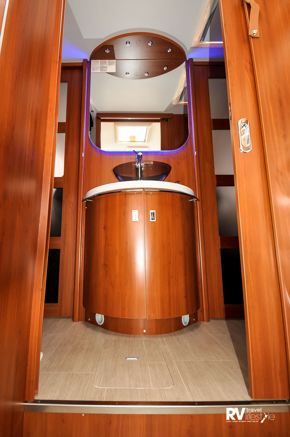 From the front to rear: entry door behind driver, kitchen and bathroom midship, large L-shaped lounge at rear with electric drop-down bed in the ceiling. Dining behind the passenger cab area, both cab seats swivel to the rear