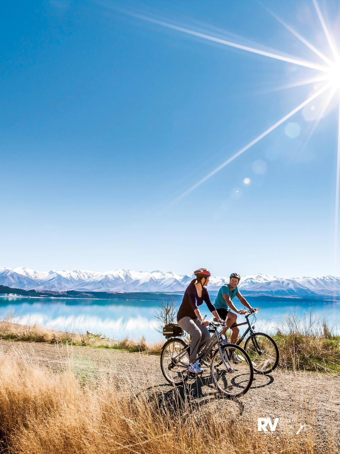 Cyclists riding alongside Lake Pukaki on a perfect day. Photo by Miles Holden