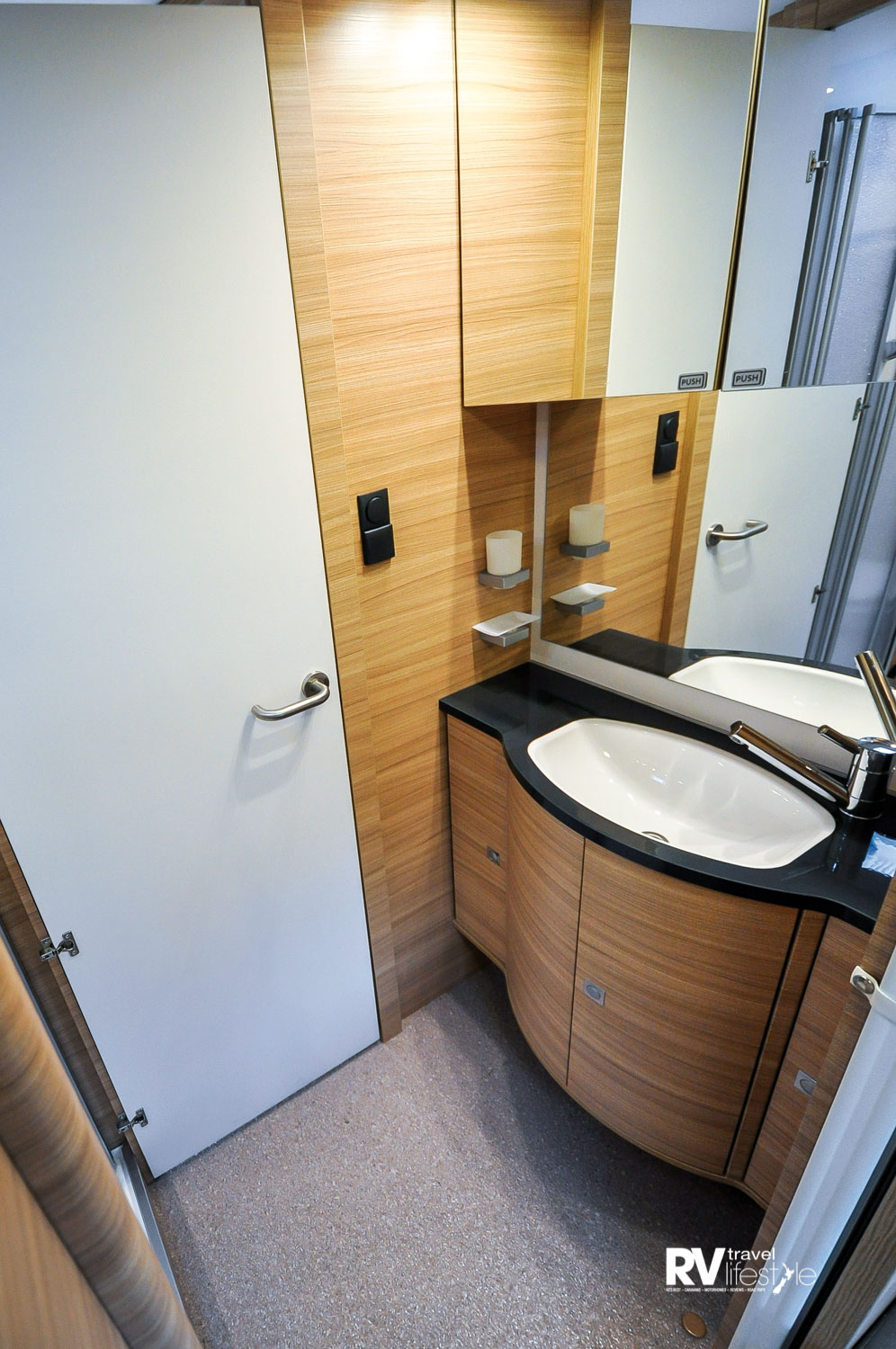 The bathroom with vanity unit, storage below, mirrored wall shelf unit, the shower/toilet is to the near-right of this image. This is on the left side of the vehicle looking to the rear, opposite the shower/toilet door