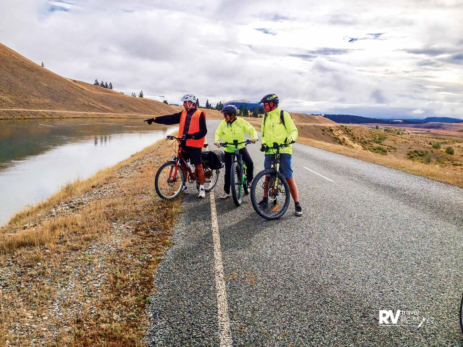 Chris and our e-biking mates Libby and Dave, spotting fish in the Tekapo–Pukaki canal