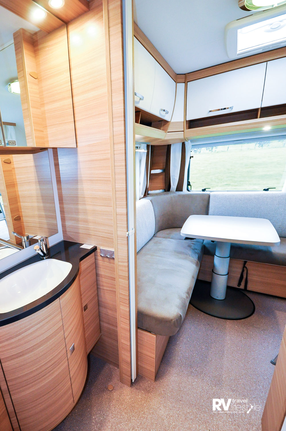 The bathroom door opens between the rear bunk-lounge area and main bed space