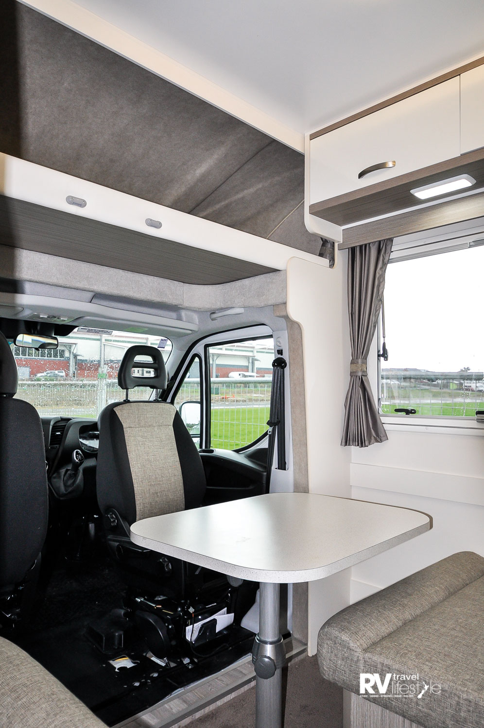 The overhead Luton space above the cab, small dinnette table and seating behind