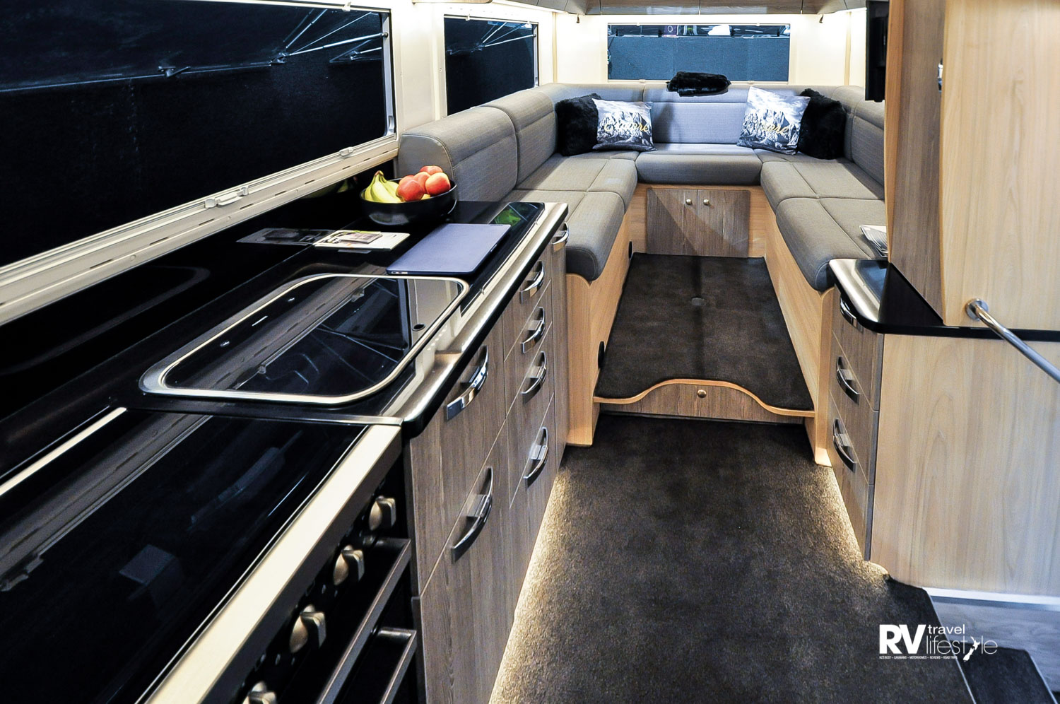 Habitation entry is on the left passenger side mid vehicle, kitchen opposite, large lounge-dining area at the rear, plenty of overhead locker storage
