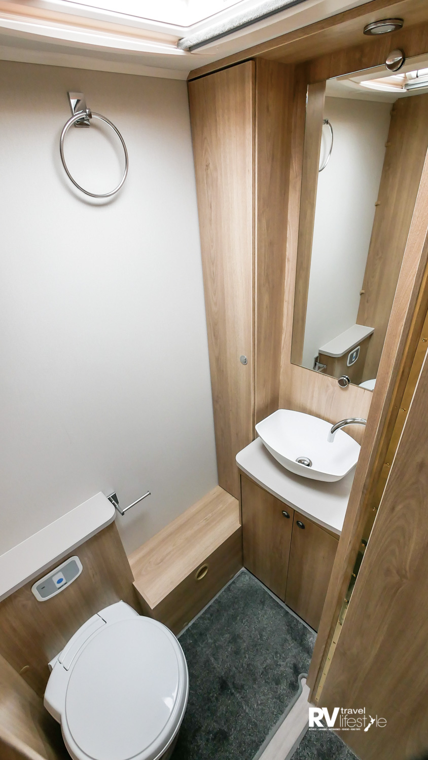 Separate toilet ensuite with vanity, composite vanity basin, and long shallow cupboard storage to the left. Electric flush cassette swivel toilet, roof vent above