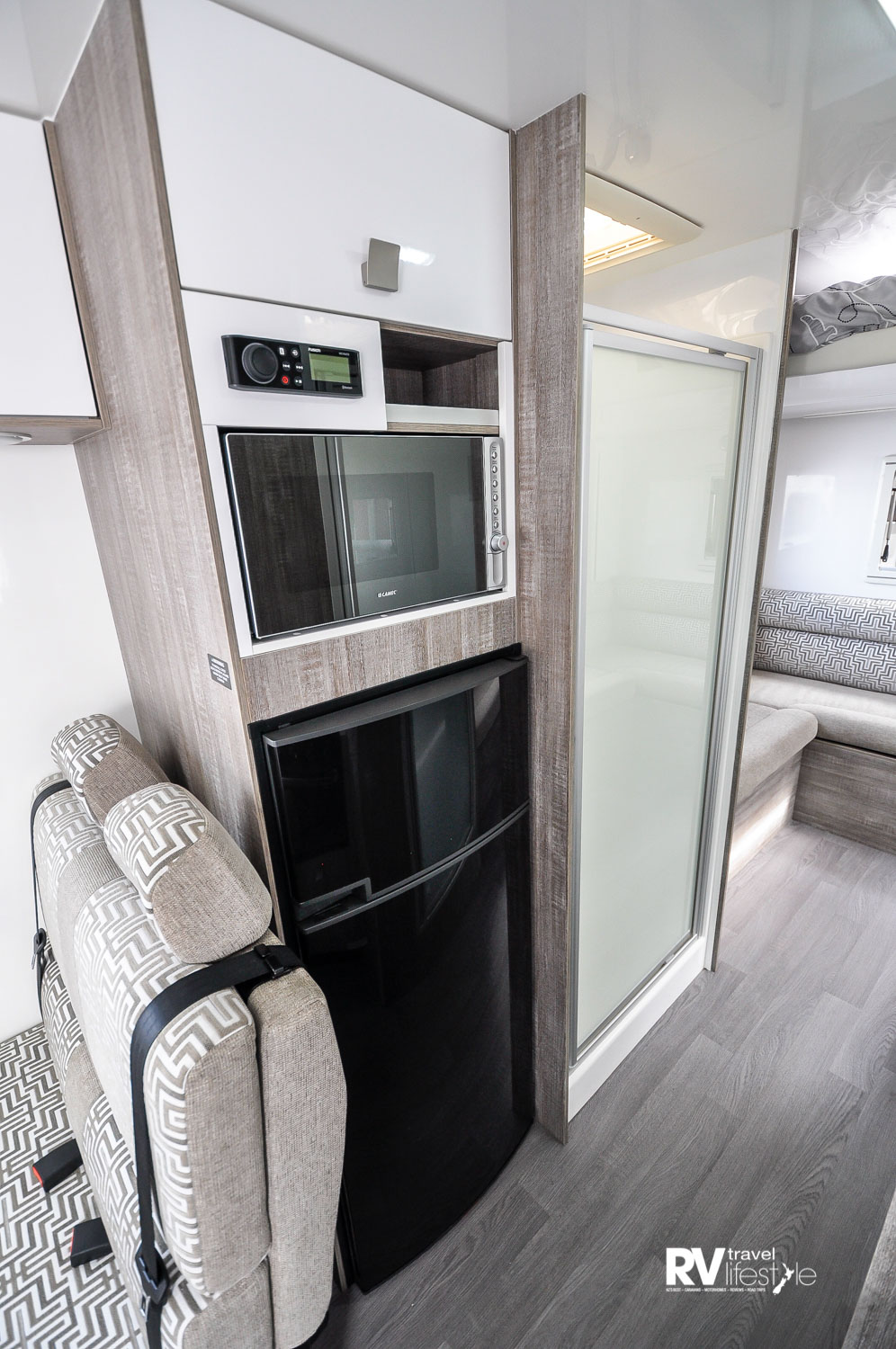 Behind the dinette we move to the utility tower with 190L auto three-way fridge, microwave and entertainment centre above, storage above that – walk through to the shower en-suite and the rear lounge