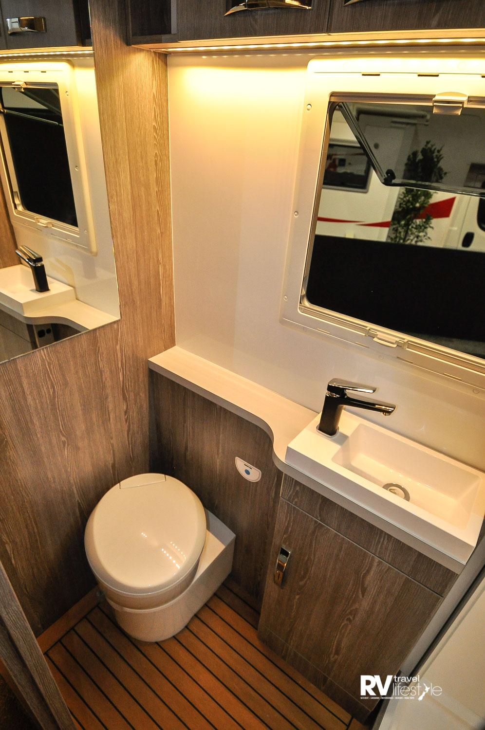 A Thetford 20L electric flush pedestal toilet sits to the left of the shower unit, a window for ventilation and light, vanity sink, shelf and un-der cupboard storage, as well as overhead locker storage – again love that teak floor