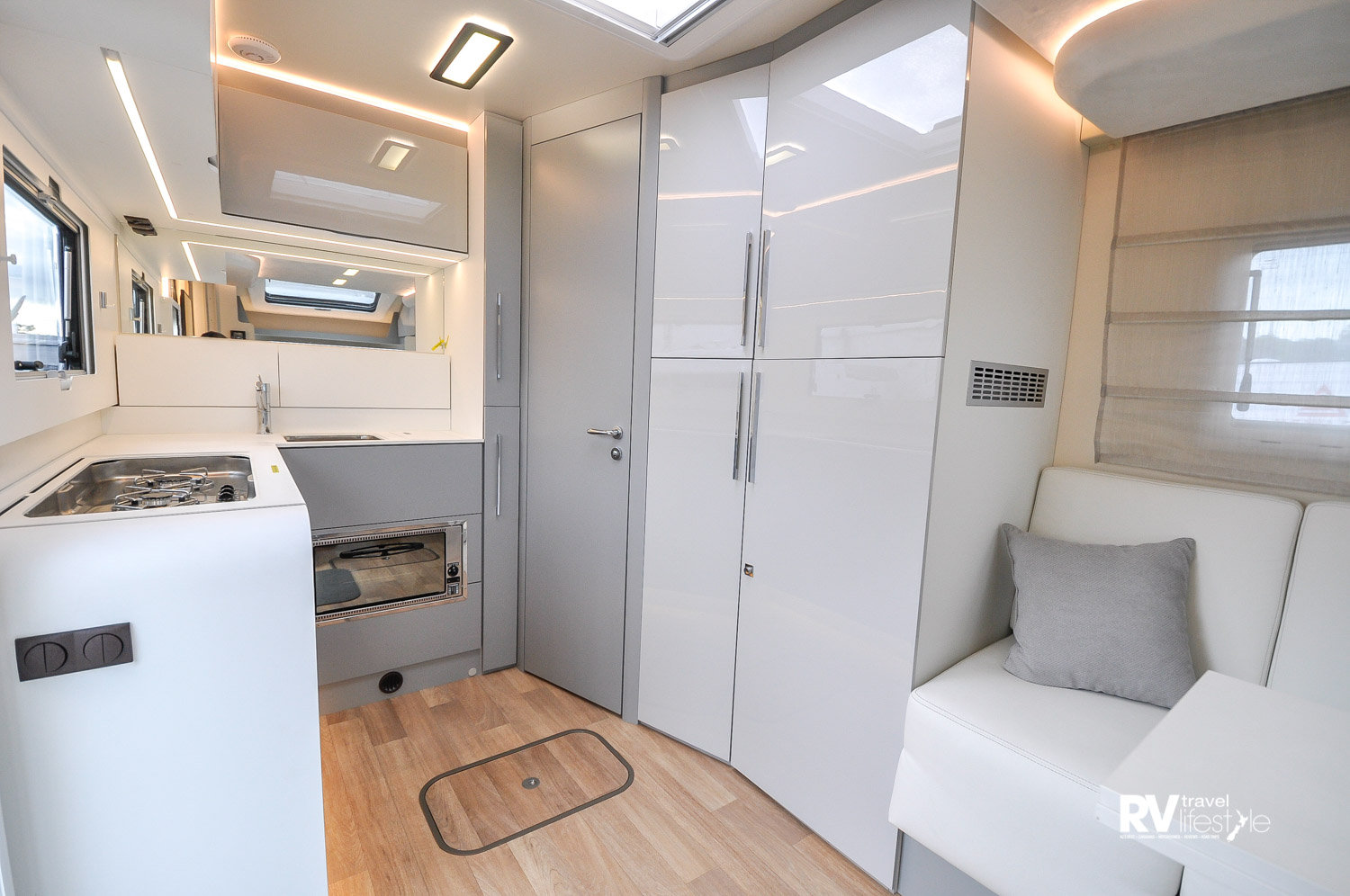 Stepping into the vehicle the kitchen is to the left in the rear, bathroom in the opposite rear corner, and wardrobes and fridge behind those stylish high gloss doors. Bed/lounge/entertainment area is in the front behind the cab, with swivel seats to add to the seating area
