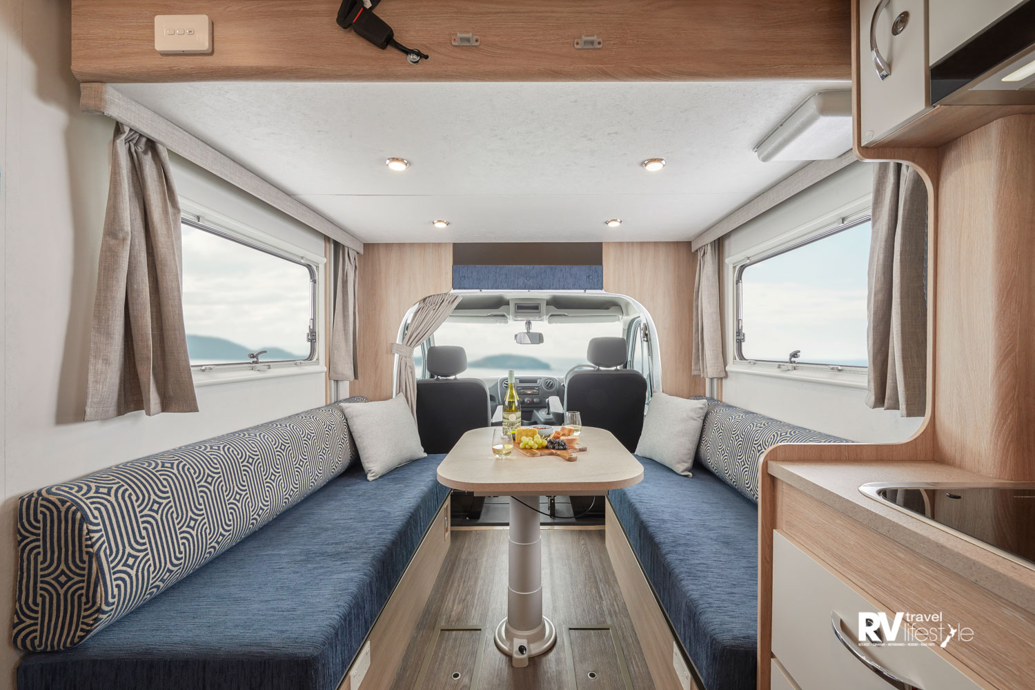 Two long lounge seats with fully adjustable table in the middle, storage hatches on the floor, and in the Luton overcab area even more storage. You don't notice the ceiling is the hidden second bed