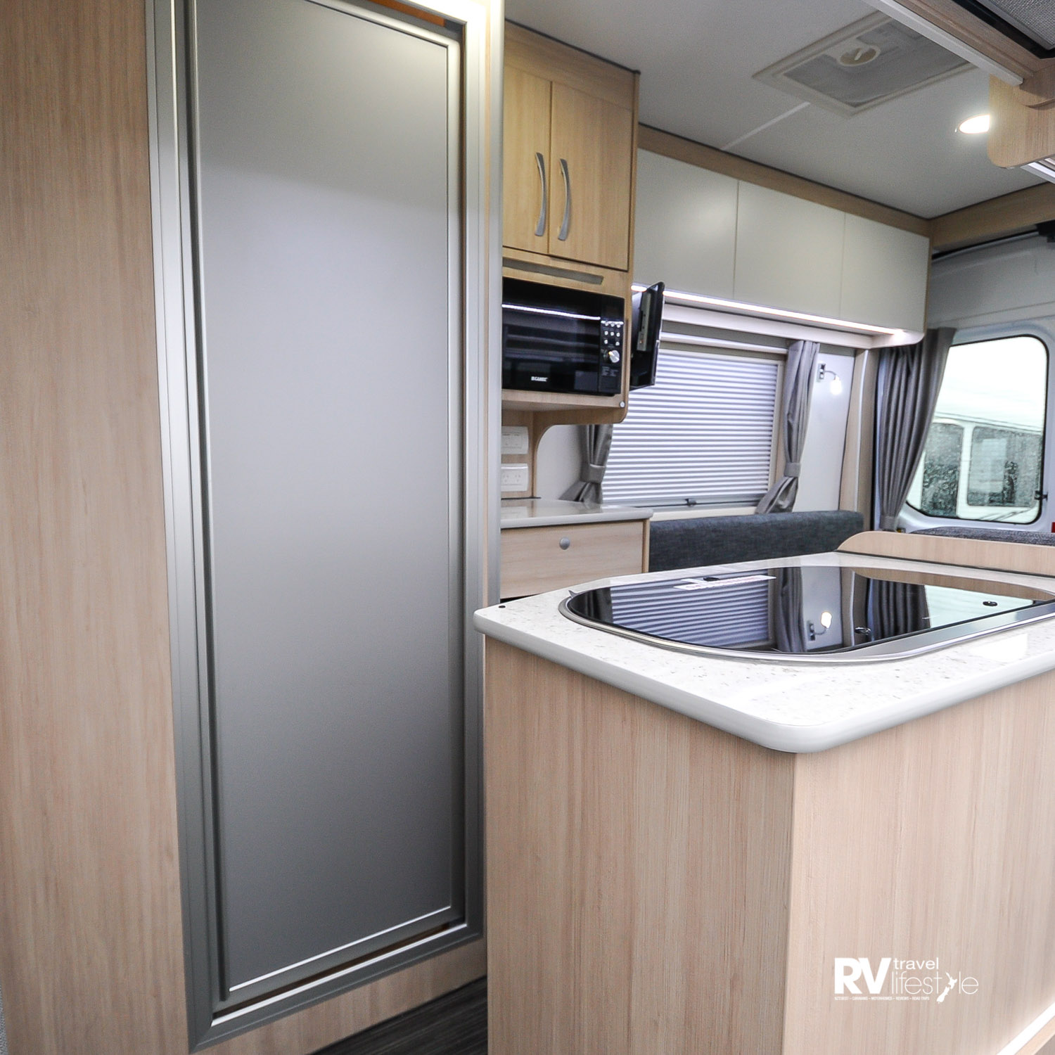 Open the side sliding door and you step up into the camper, kitchen on right, bathroom unit opposite, cab on the left