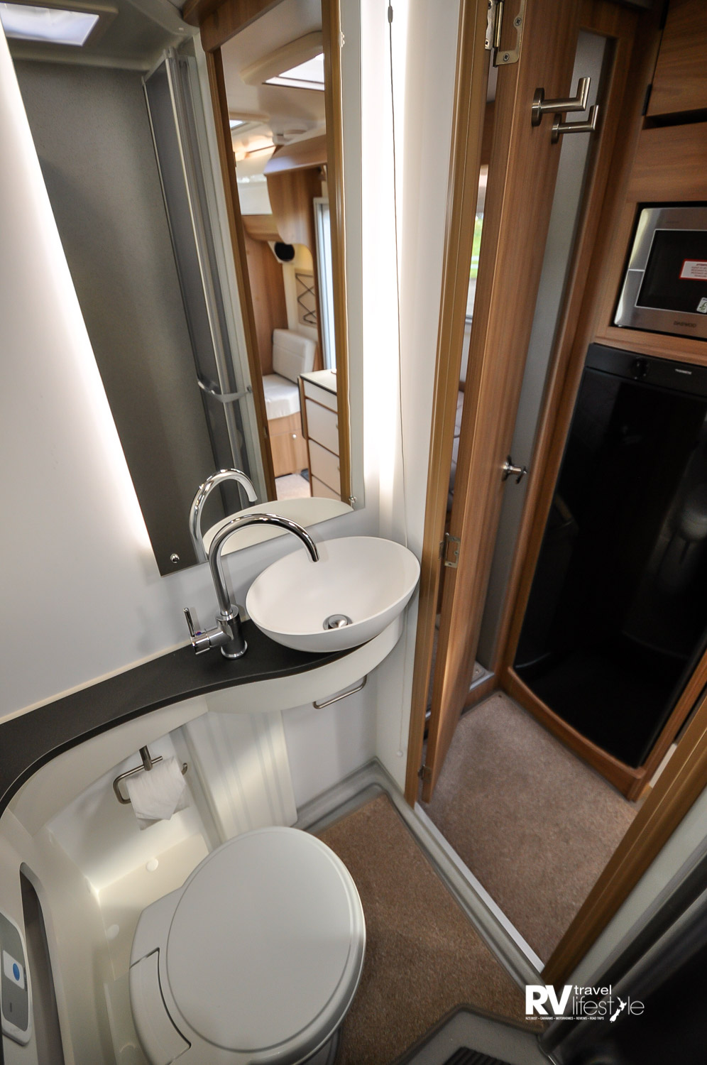 A curvy finish to the bathroom to accommodate the round sink, towel hook underneath, toilet roll holder fitted, storage behind the toilet which is a 12V electric flush pedestal toilet