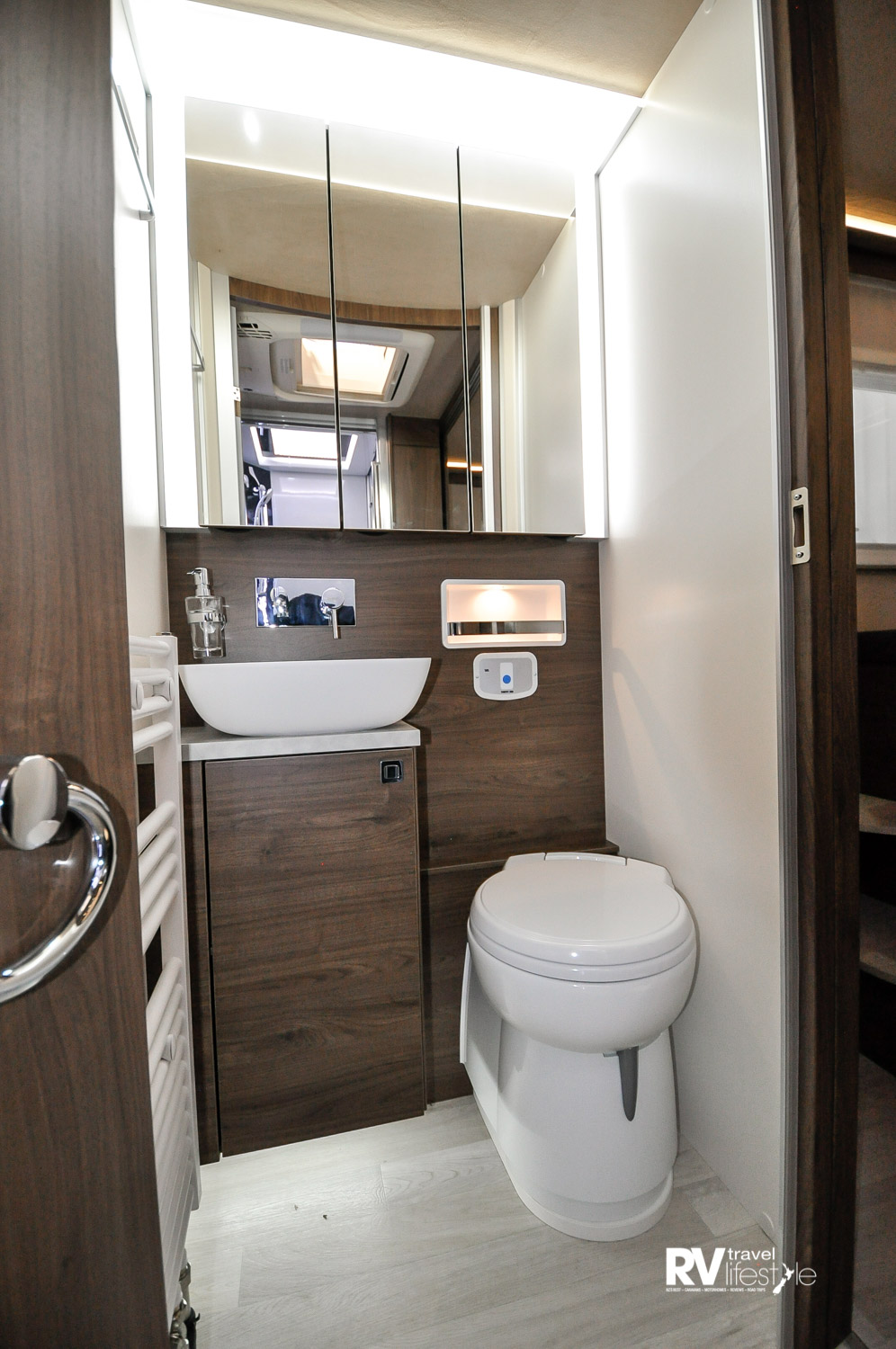 A well-lit en-suite toilet. On the left wall a radiator heater, ceramic cassette electric flush toilet. The vanity has storage underneath; the mirrored cabinet opens to offer multiple storage shelves. Check out the tap on the wall, the inset lit storage shelf behind the toilet. A fixed soap holder is so handy