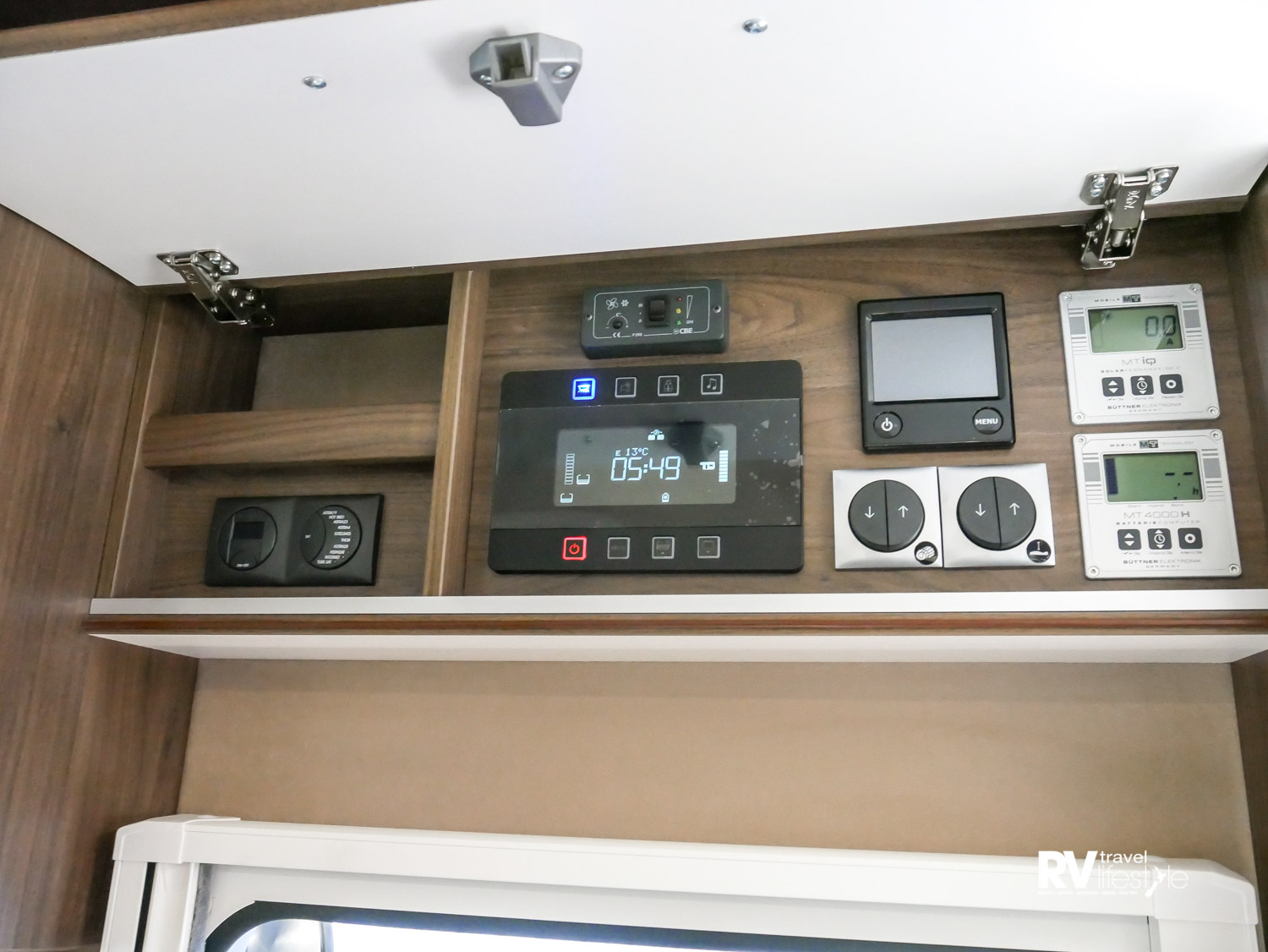 The monitors and controls in one space above the door. Easy-to-use controls for the ceiling bed and electric awning