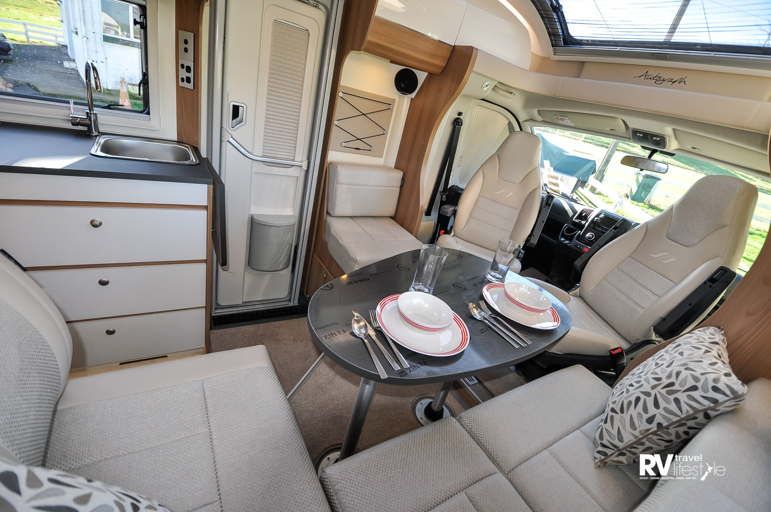 The dinette area set up for dining, the habitation entry door is on the passenger left side of the vehicle