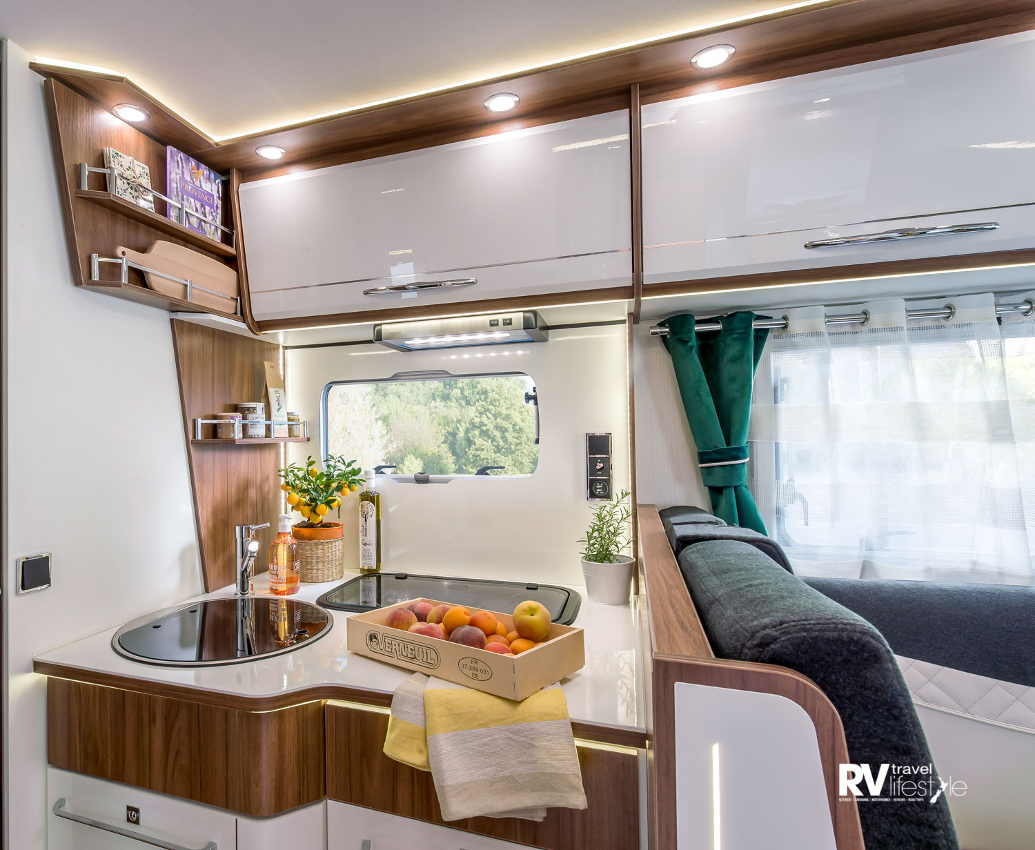 The kitchen has a deep bench, a window with back splash, opening window with screens and blinds, rangehood overhead