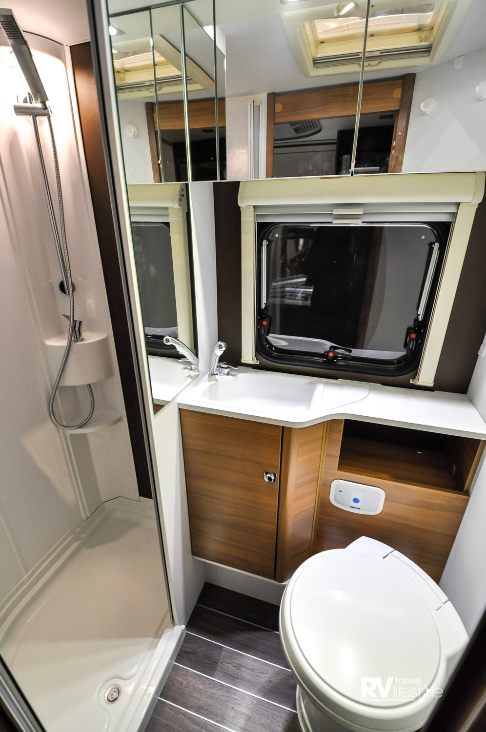 XL 660 SCS Motorhome – Good looking bathroom with full-sized separate shower, pedestal-cassette electric flush toilet, cupboards and storage areas, as well as a window and vent for ventilation