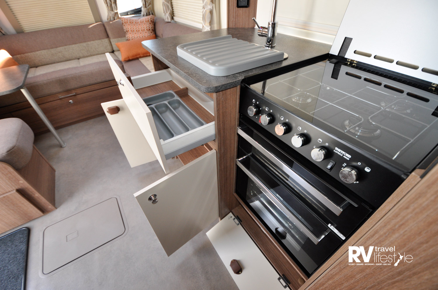 A full oven with storage underneath, four-burner hob on top with glass cover as well as a bench cover that is level with the main bench. Utility drawer and cupboards under the sink