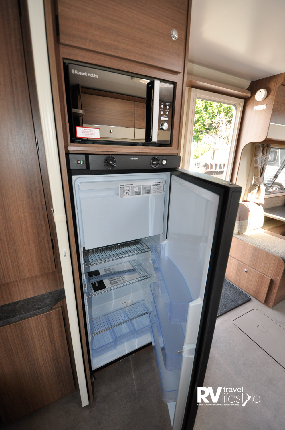 Fridge with freezer unit inside, microwave above this and storage cupboard above that