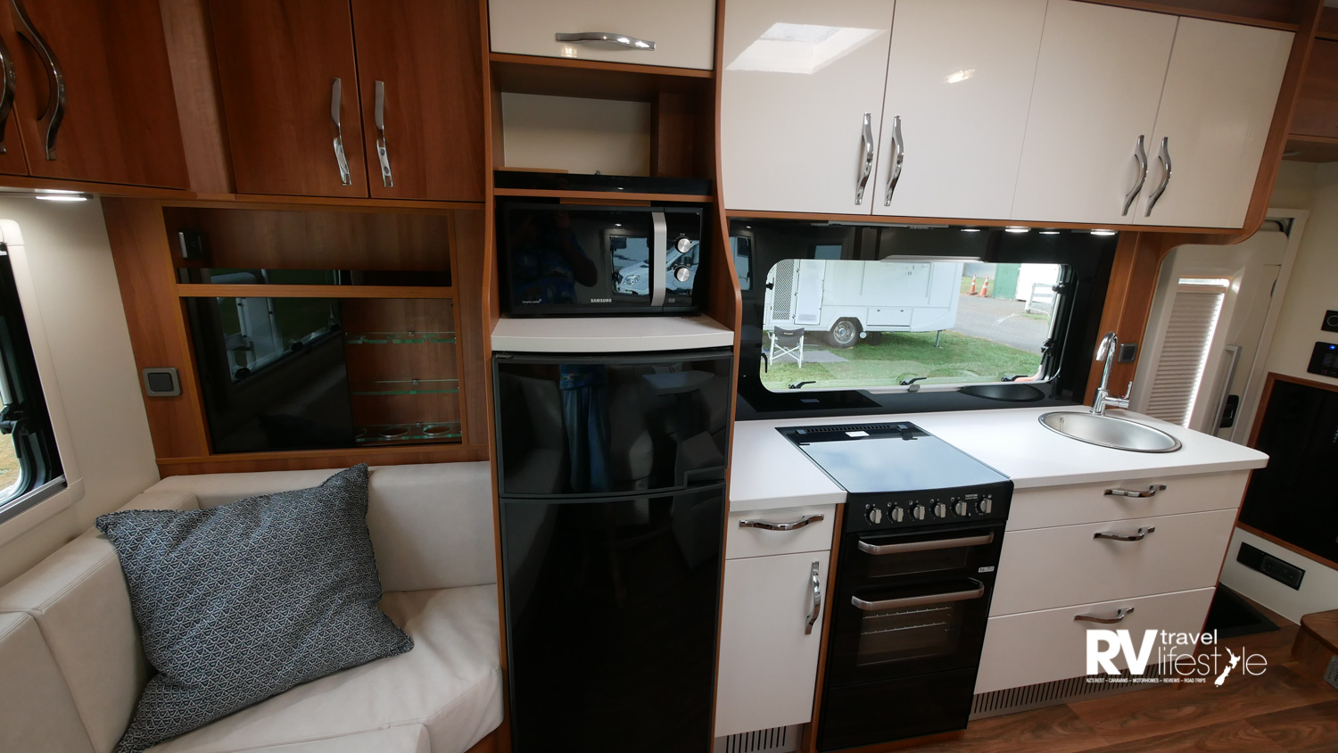A stylish kitchen setup with 195L AES Dometic fridge, full-sized oven with four-burner gas hob, oven and separate grill, and HPL kitchen worktops