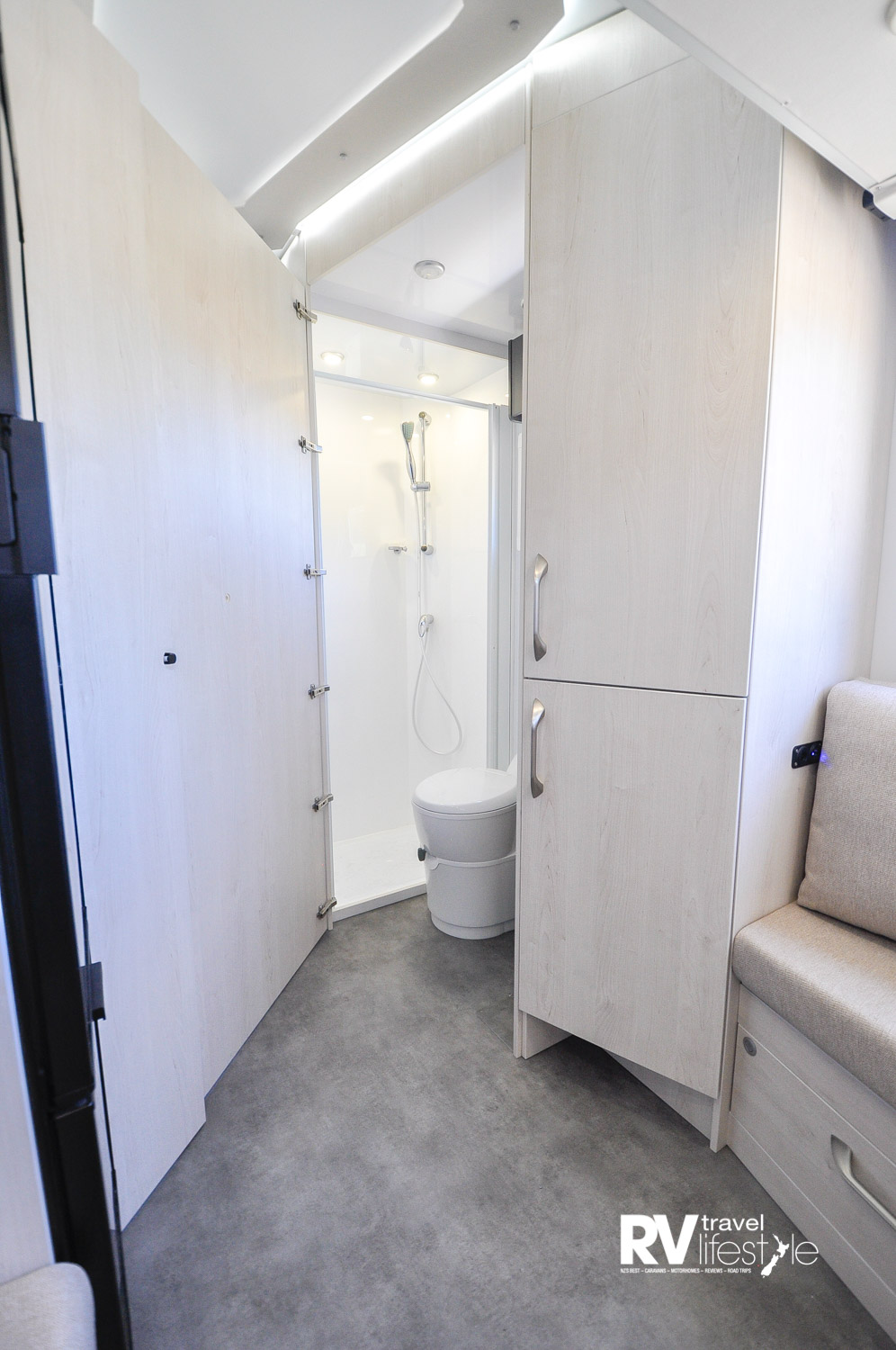 The midship bathroom has a full height shower, pedestal toilet; the door opens across to the kitchen bench to create a privacy area.