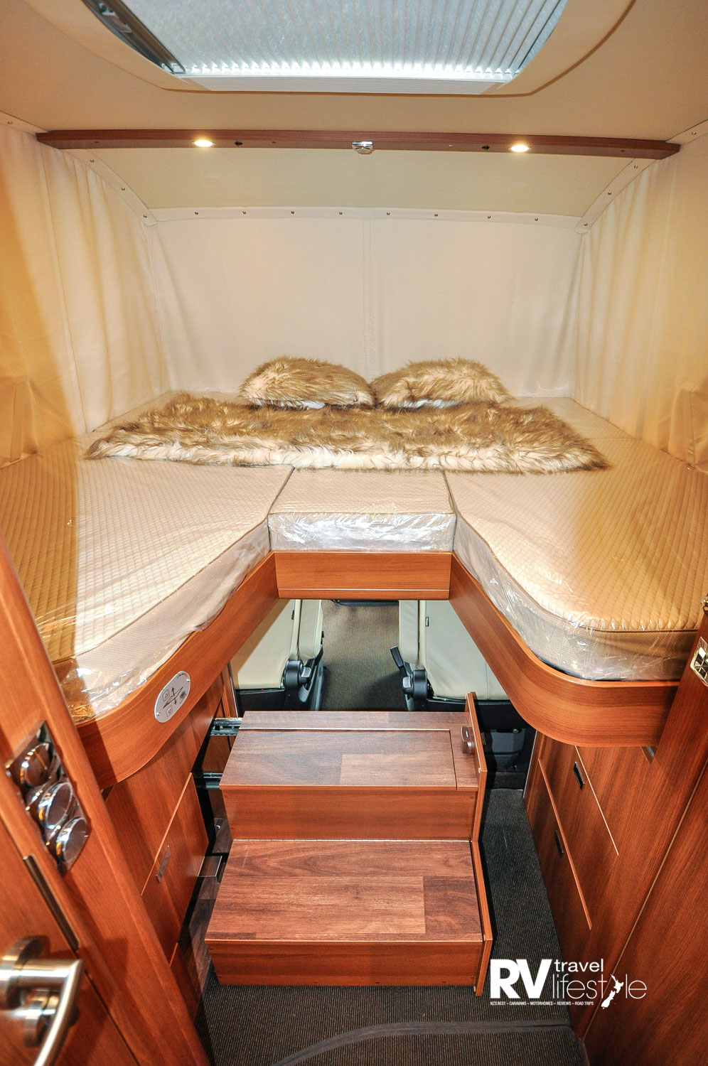 At the push of a button the bed unpacks itself and descends to shut off the front cab area completely. Steps come out of the cupboard for bed entry. The steps have storage in them as well, so all spaces used