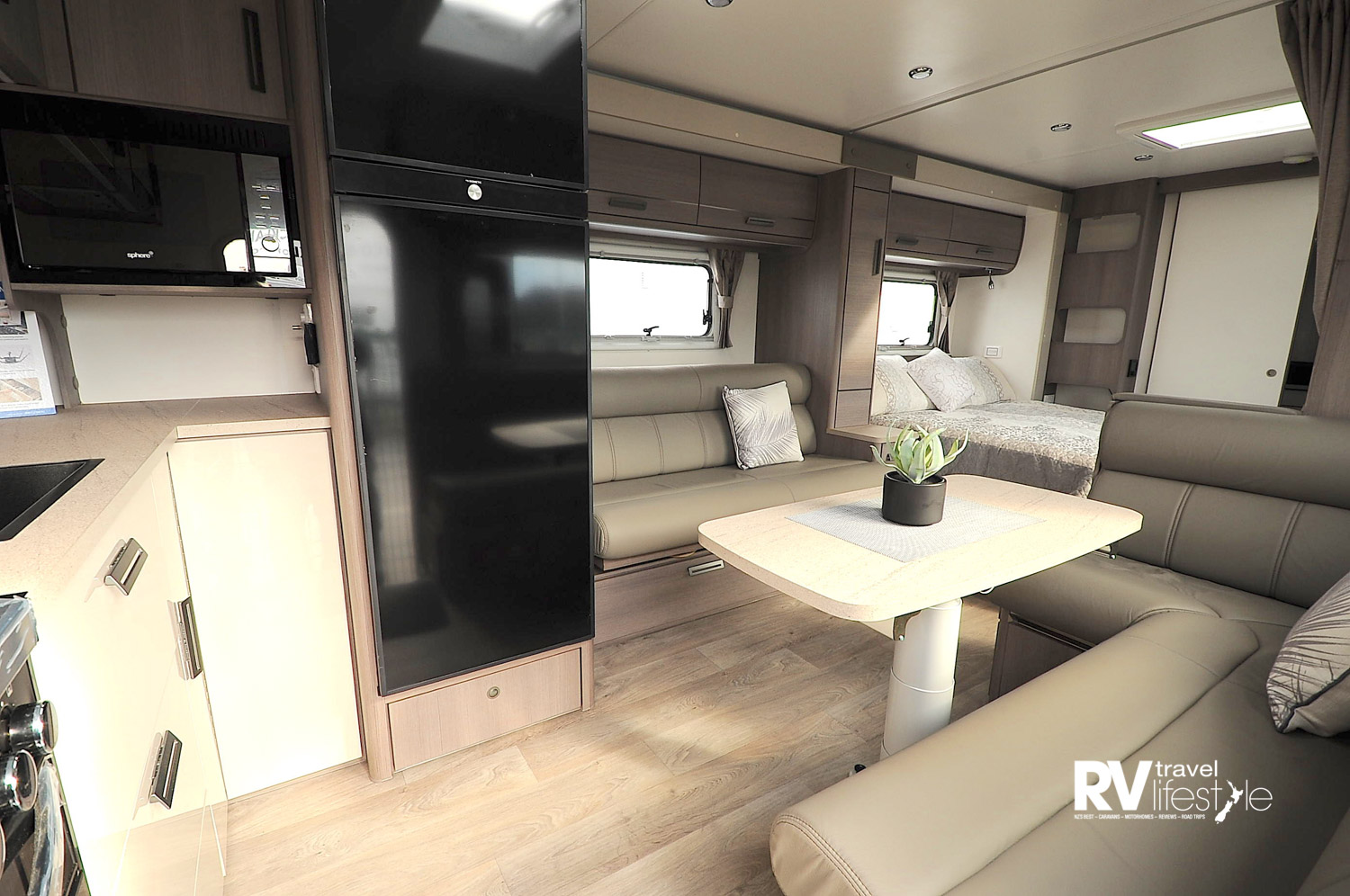 Stepping up into the caravan kitchen is full width to the left in the nose of the caravan, 241L fridge-freezer opposite; dining seating that converts to spare bed, another lounge opposite, bedroom separates by curtain, and full width rear bathroom