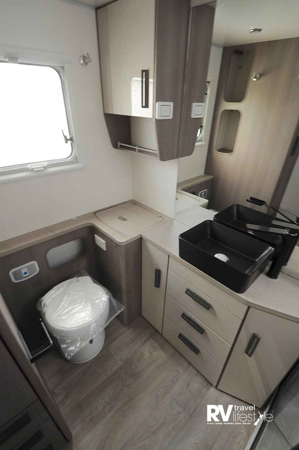 The full width bathroom, plenty of storage, the lift-up lid in the corner is home to a 3kg washing machine, toilet is electric flush cassette; full-sized shower on the right out of shot