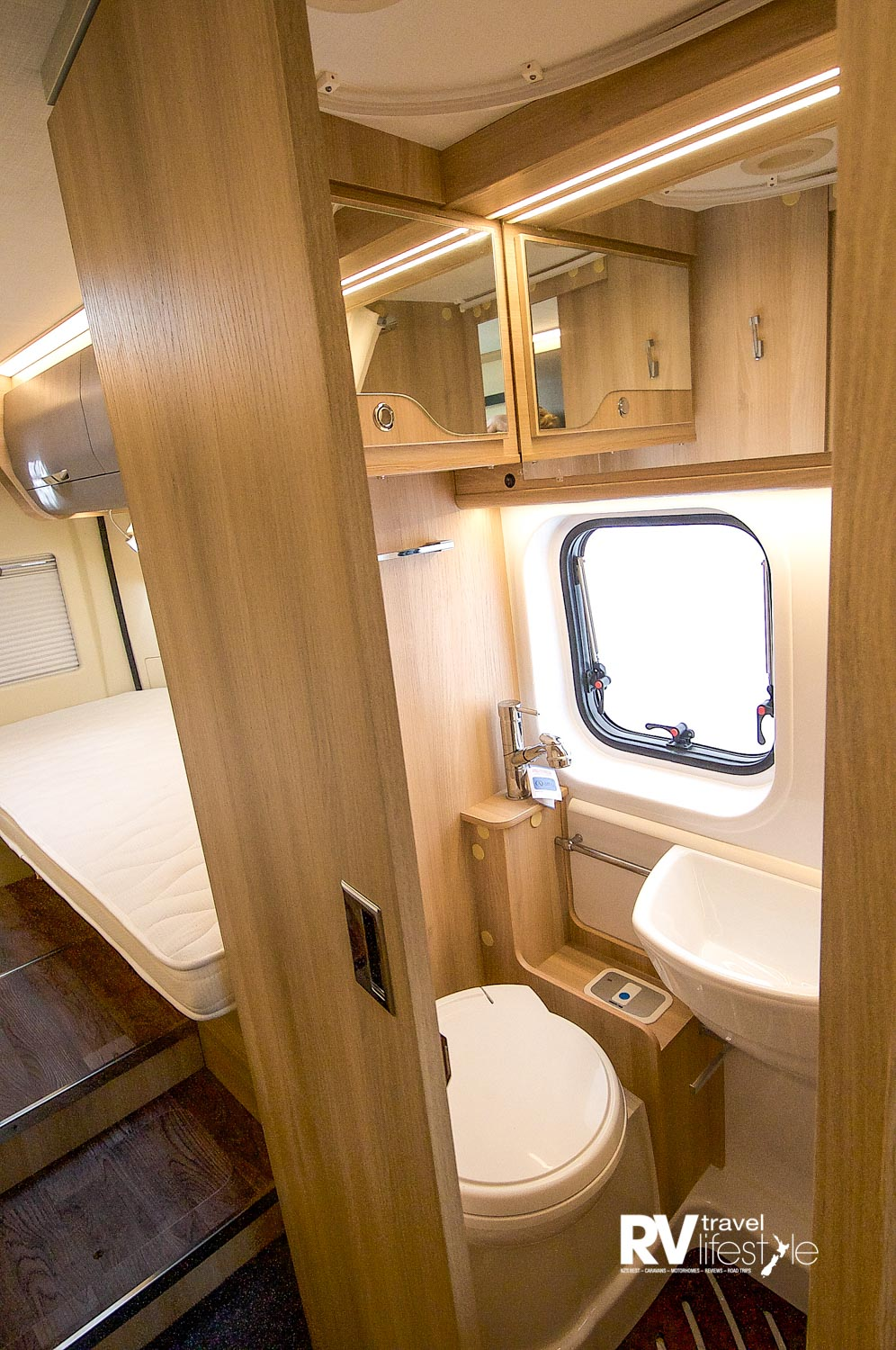 I like the sliding door entry, electric flush toilet, shower box with small vanity sink, window and overhead storage – mirrors make the area seem larger