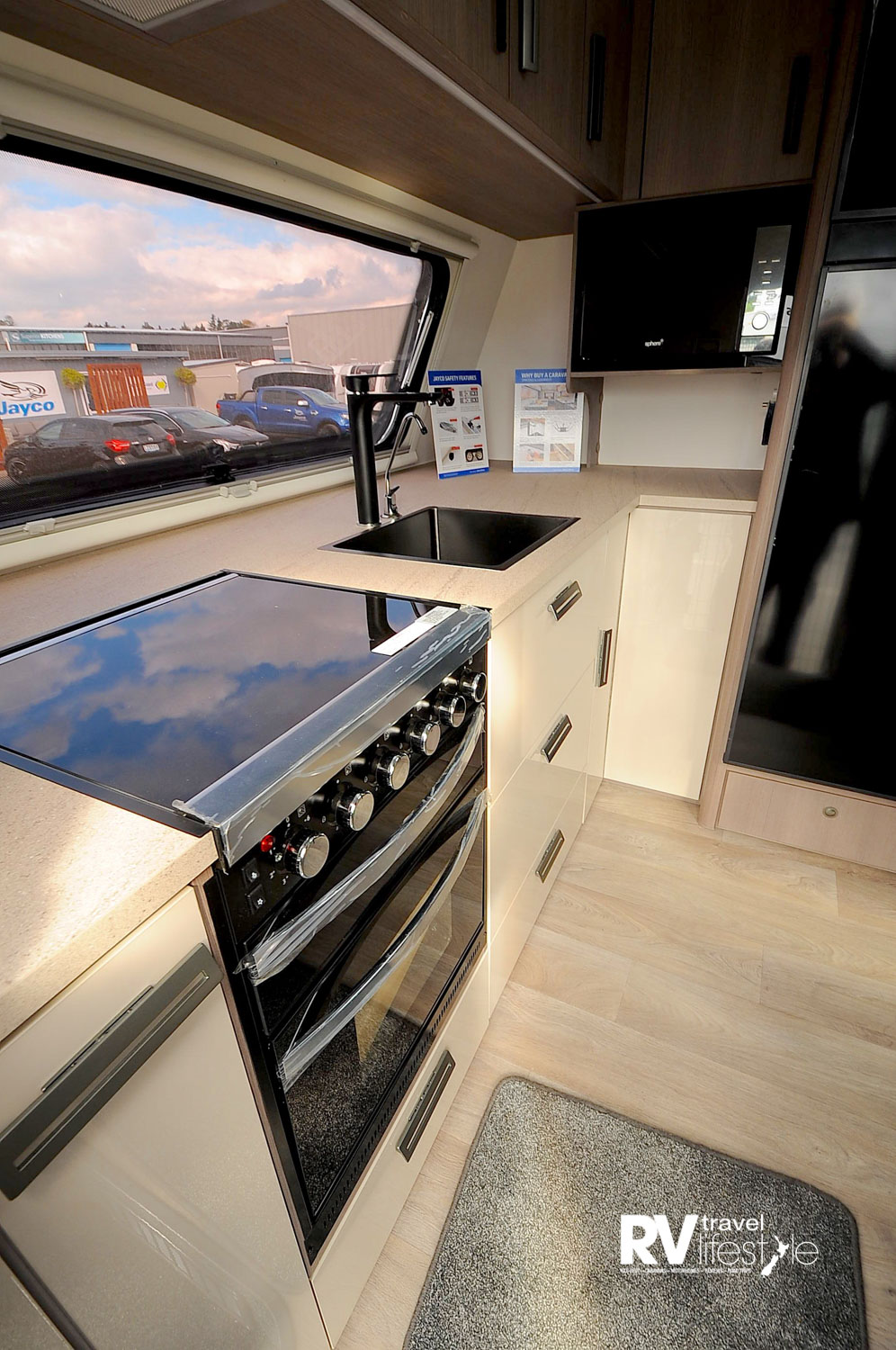 The full-width kitchen offers full-sized oven with separate grill, four gas hobs, large inset sink, drawers and pull-out pantry storage, substantial storage in the overhead lockers, and a large microwave