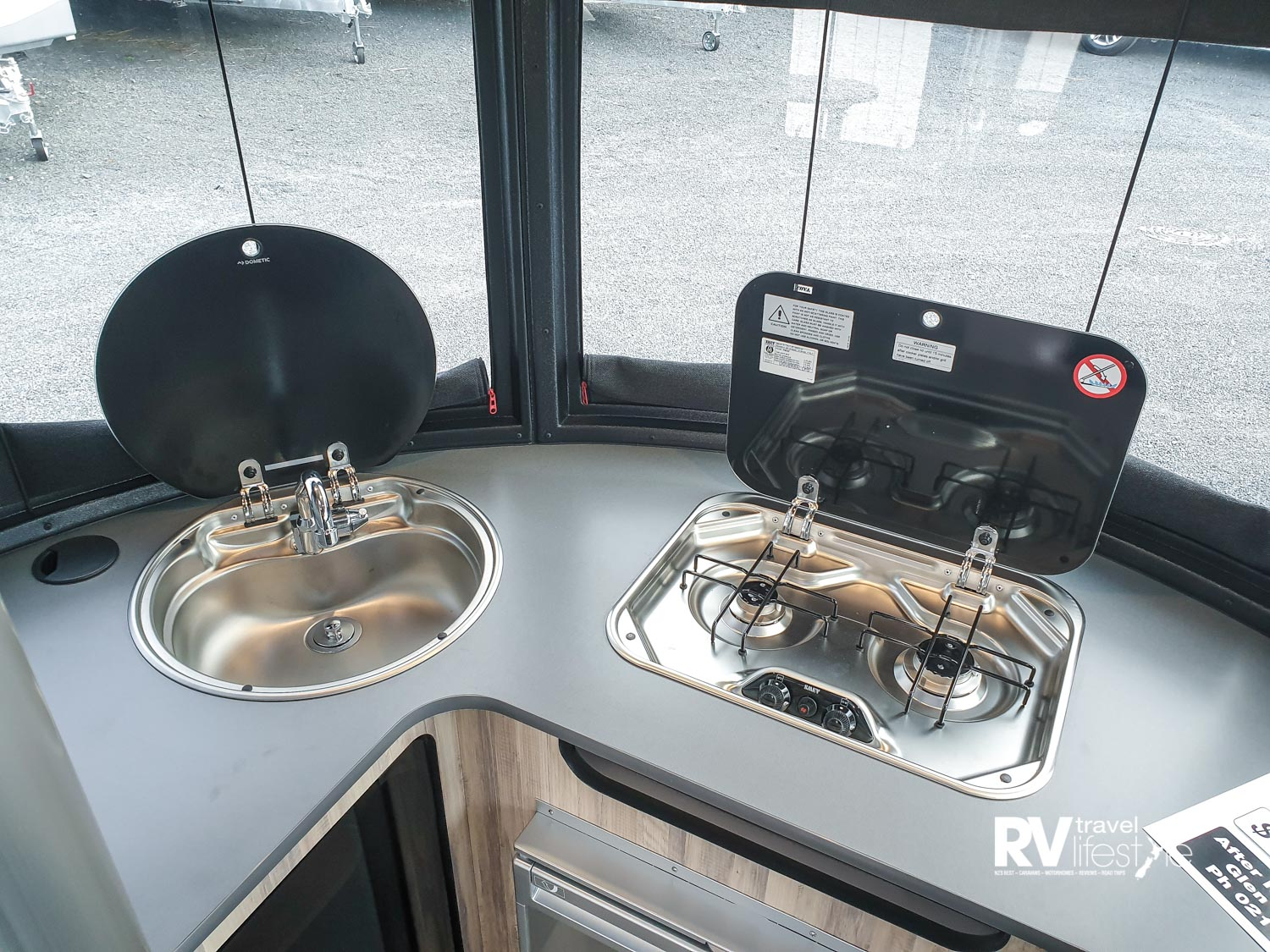 Nifty kitchen bench, sink and two-burner gas hob for cooking, both stainless steel with covers for extra preparation space. Note the curved front windows, blinds unzip and roll down