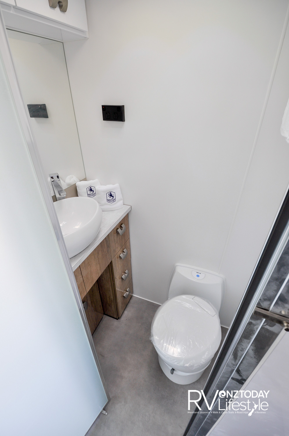 Toilet en suite with vanity unit, plenty of storage under the sink and above, pedestal electric flush cassette toilet