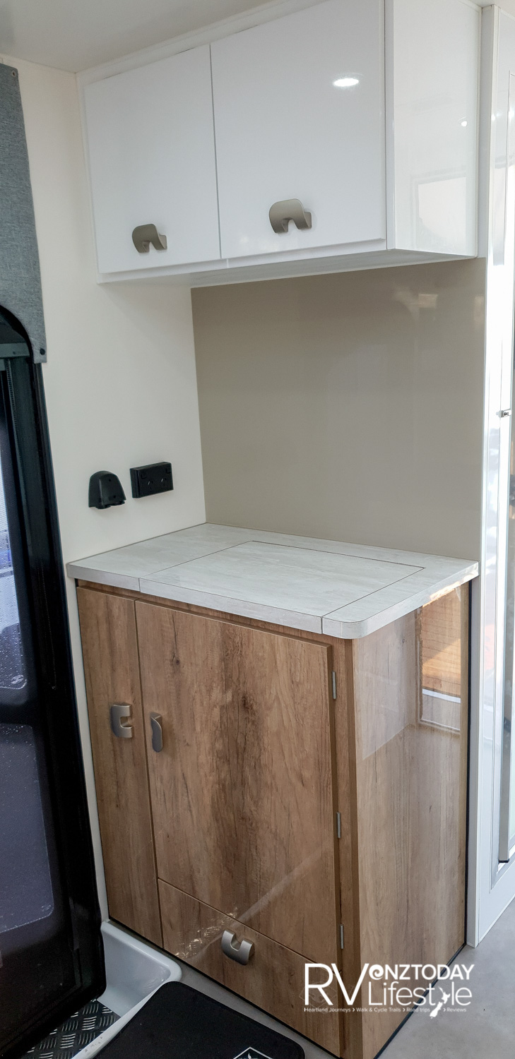 Step inside the habitation door, to the left is this unit with storage above, and a washing machine within