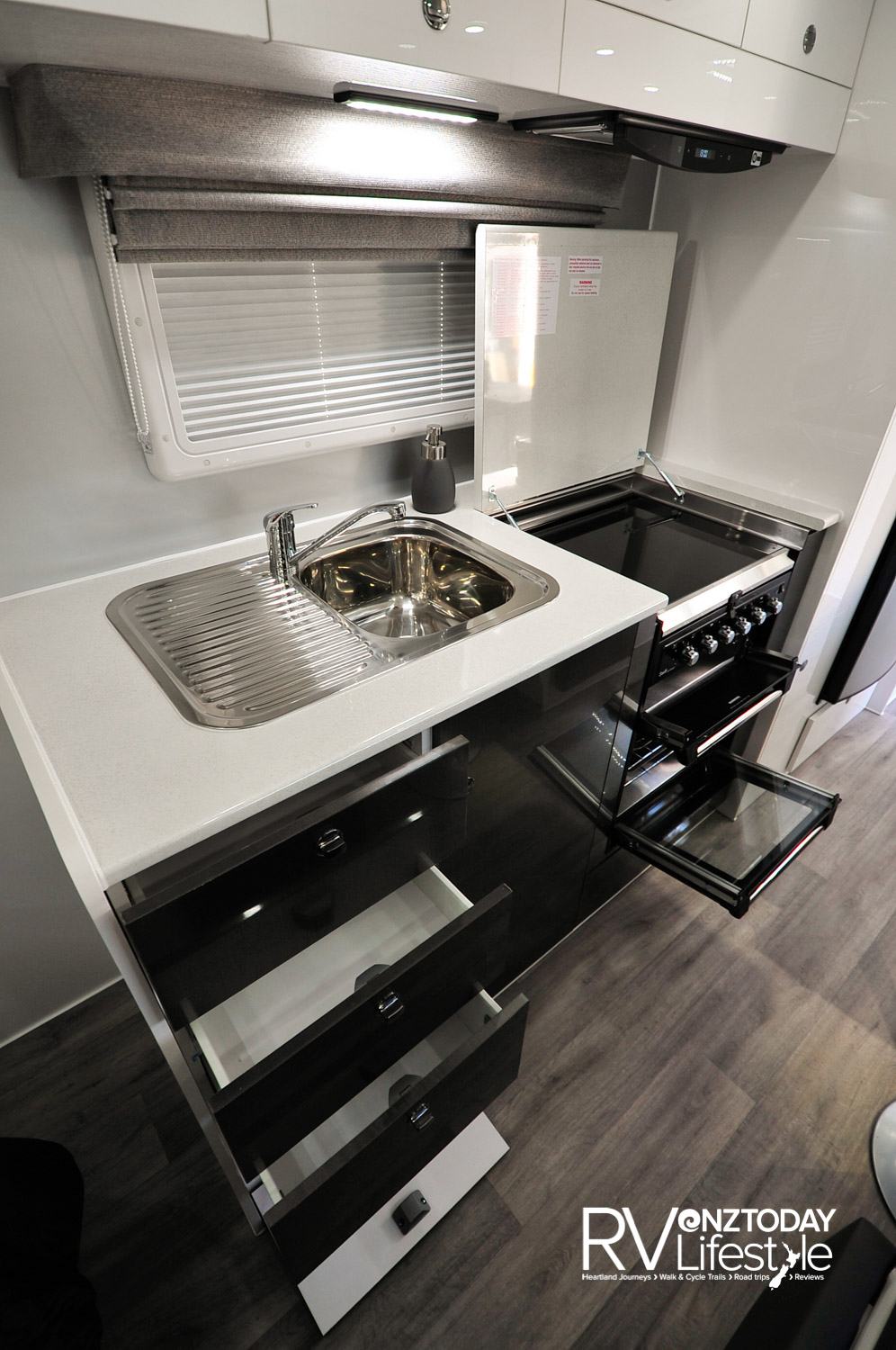 Drawers and cupboards under bench, stainless steel insert sink with drainer, the full gas oven with separate grill has three gas burners and one electric hotplate – a glass lid as well as being inset into the bench top so a benchtop lid for the unit could be fitted