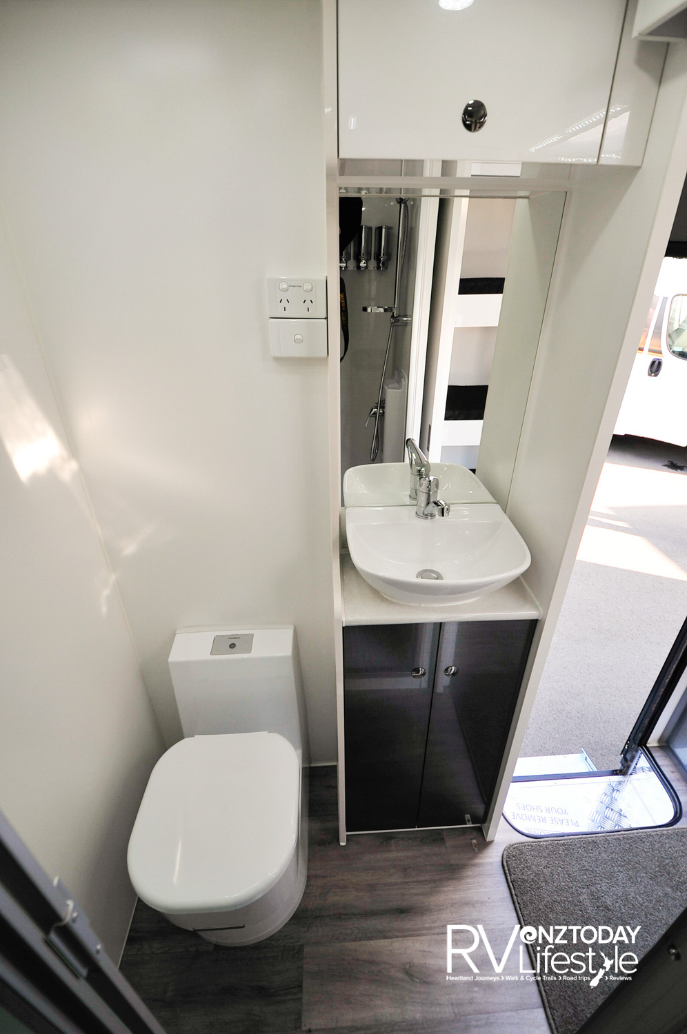 Pedestal cassette toilet with 12V electric flush. Nice compact vanity unit with storage below and above, full-sized shower opposite
