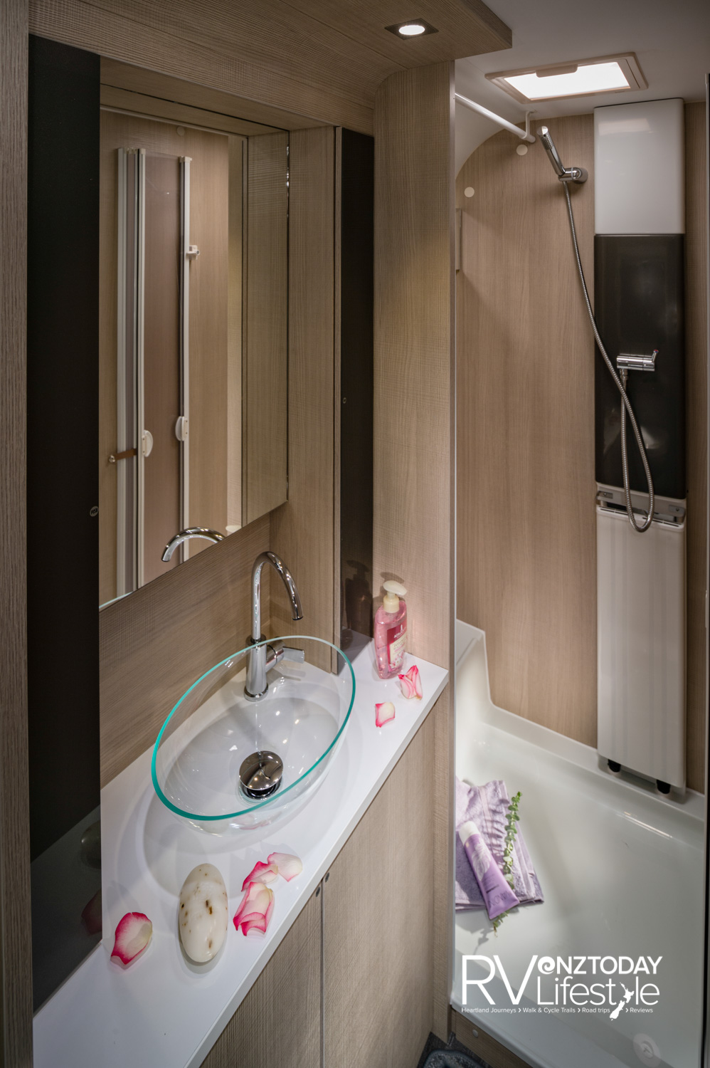 The rear full-width bathrooms offer full shower with roof vent, radiator heating to the left, vanity unit with mirrored storage, glass vanity sink, quality fixtures and fittings, storage cupboards below vanity. Cassette toilet out of picture on the left