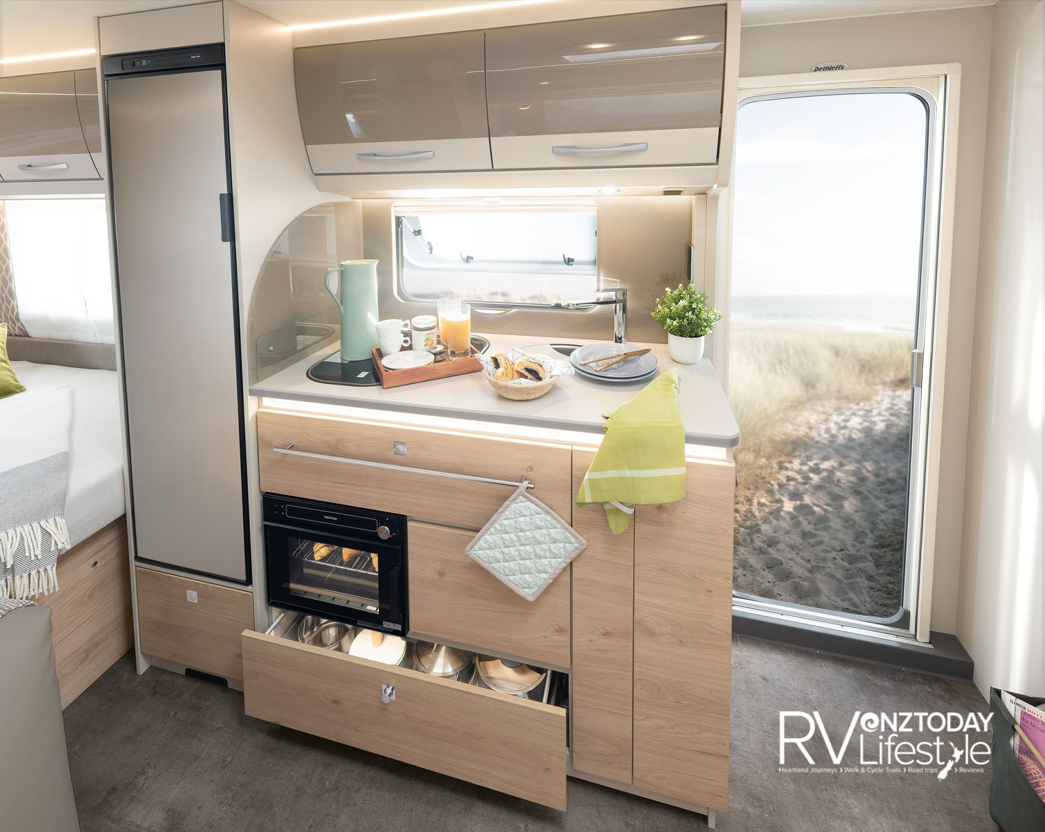 Fully featured kitchen with under-bench gas oven, three gas-burner hob on the bench, soft-close drawers and illuminated splashback. Large 142L fridge unit with storage below