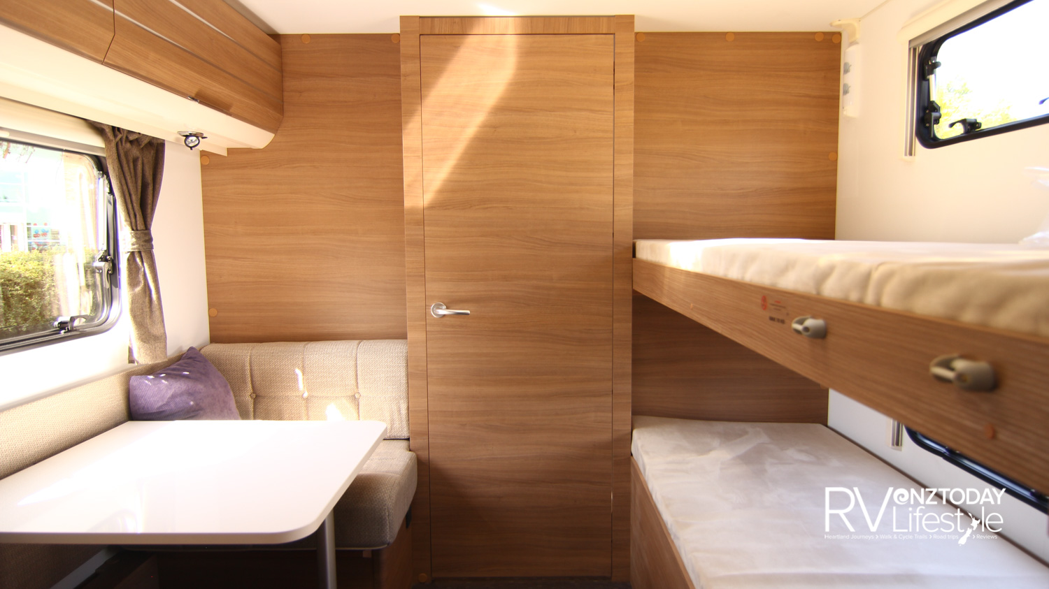 Twin bunks to the right, with individual lights and opening window for each berth. On the left a dinette table seating area, to the mid rear the full-width bathroom