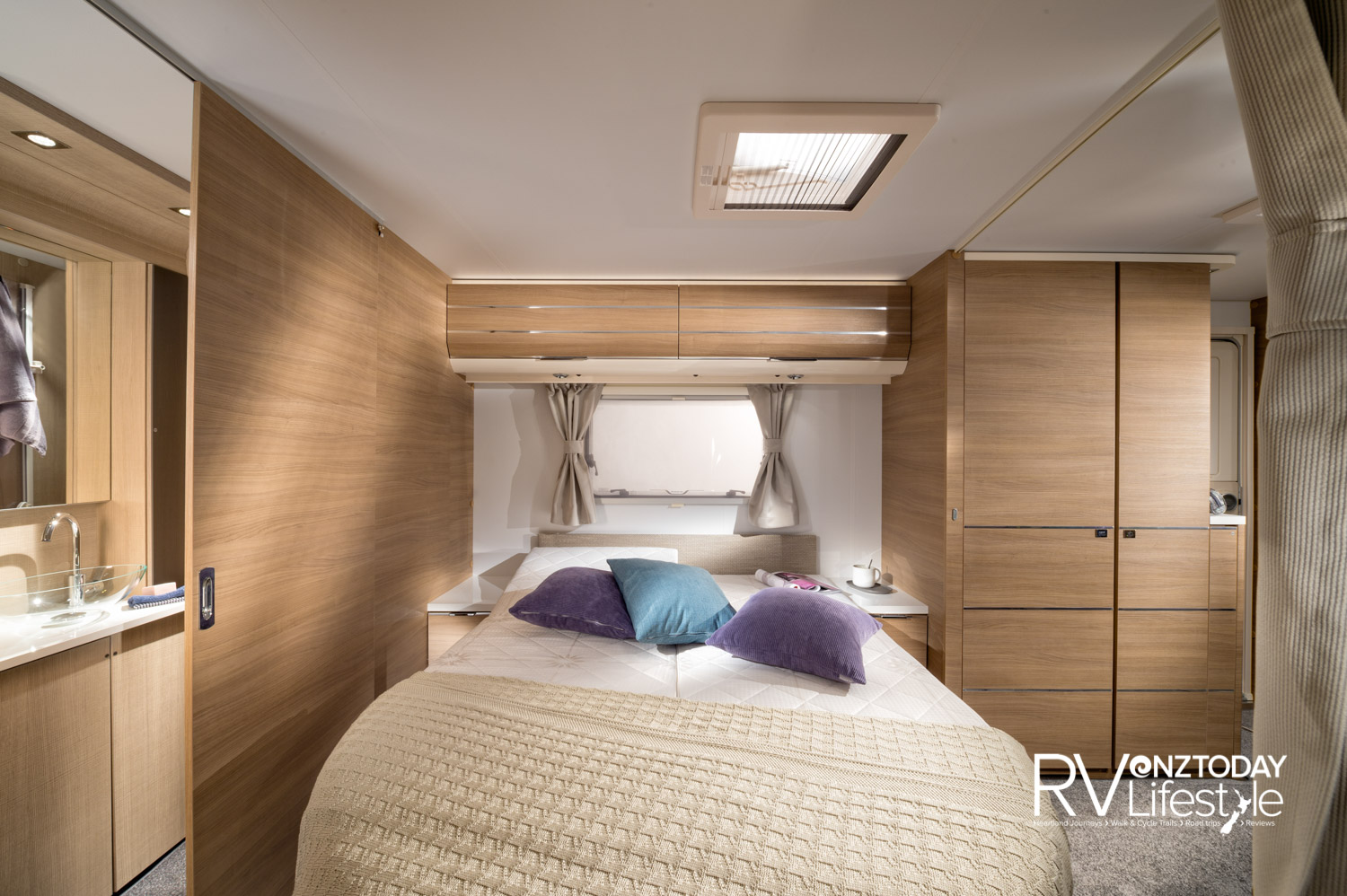 The island bed layout will be popular. Side drawers and shelf on each side, overhead locker storage with LED strip lighting effects, reading lights and privacy curtain to the rest of the living space. Drawers and wardrobe storage on the wall beside the habitation entrance door