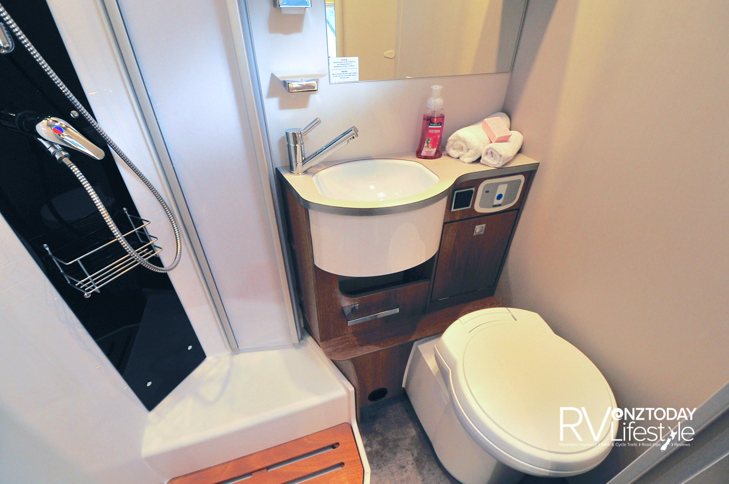 A compact bathroom, but it has it all with electric 12V flush pedestal cassette toilet, nifty vanity sink and storage, with mirror above. Separate shower box with concertina fold-back doors, adjustable showerhead, wooden tray for shower base