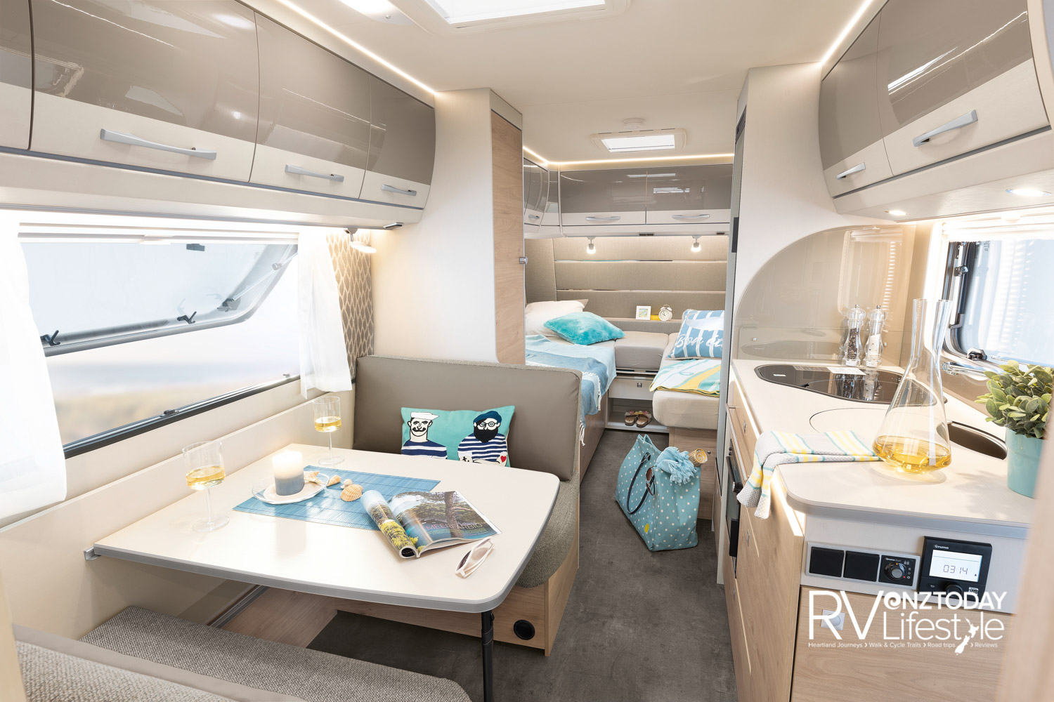 Lots to like in this bright interior: four-person dinette with large picture window, the bedroom area separated in the rear, twin single beds or convert to a large double bed, with Swiss-made mattresses