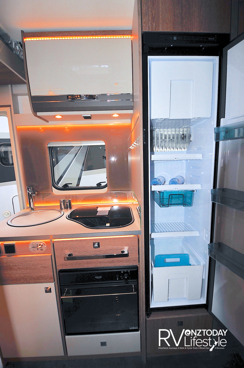 A compact kitchen, a good-sized tower fridge with freezer box. Under-bench gas oven with storage drawers above and below. Covers over the stainless sink and gas hob increase the useable space, and a bench extension is on the end. Splashback, and opening window behind, with more storage overhead. Lots of ambience strip-lighting here as well as LED spotlights